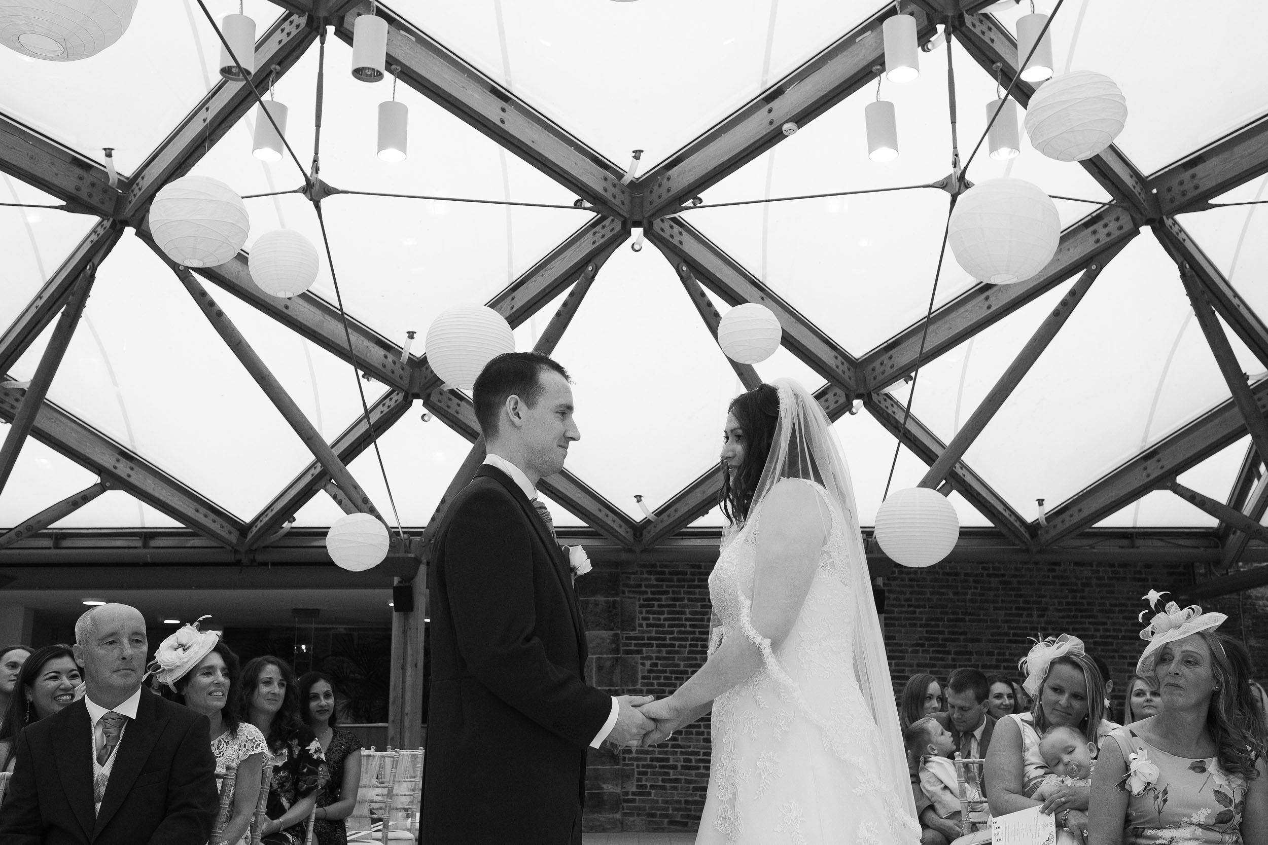 Black and white photo of bride and groom holding hands during wedding ceremony