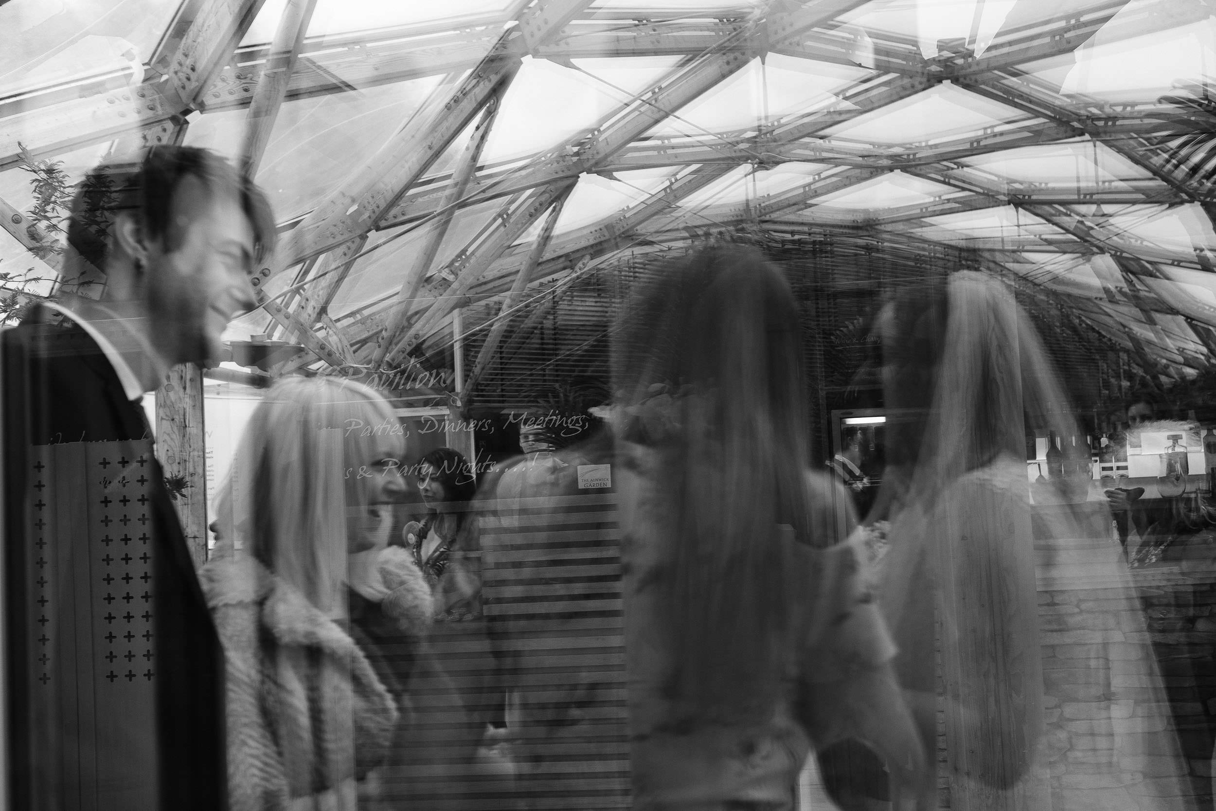 Black and white photo of reflections of bride and guests in window