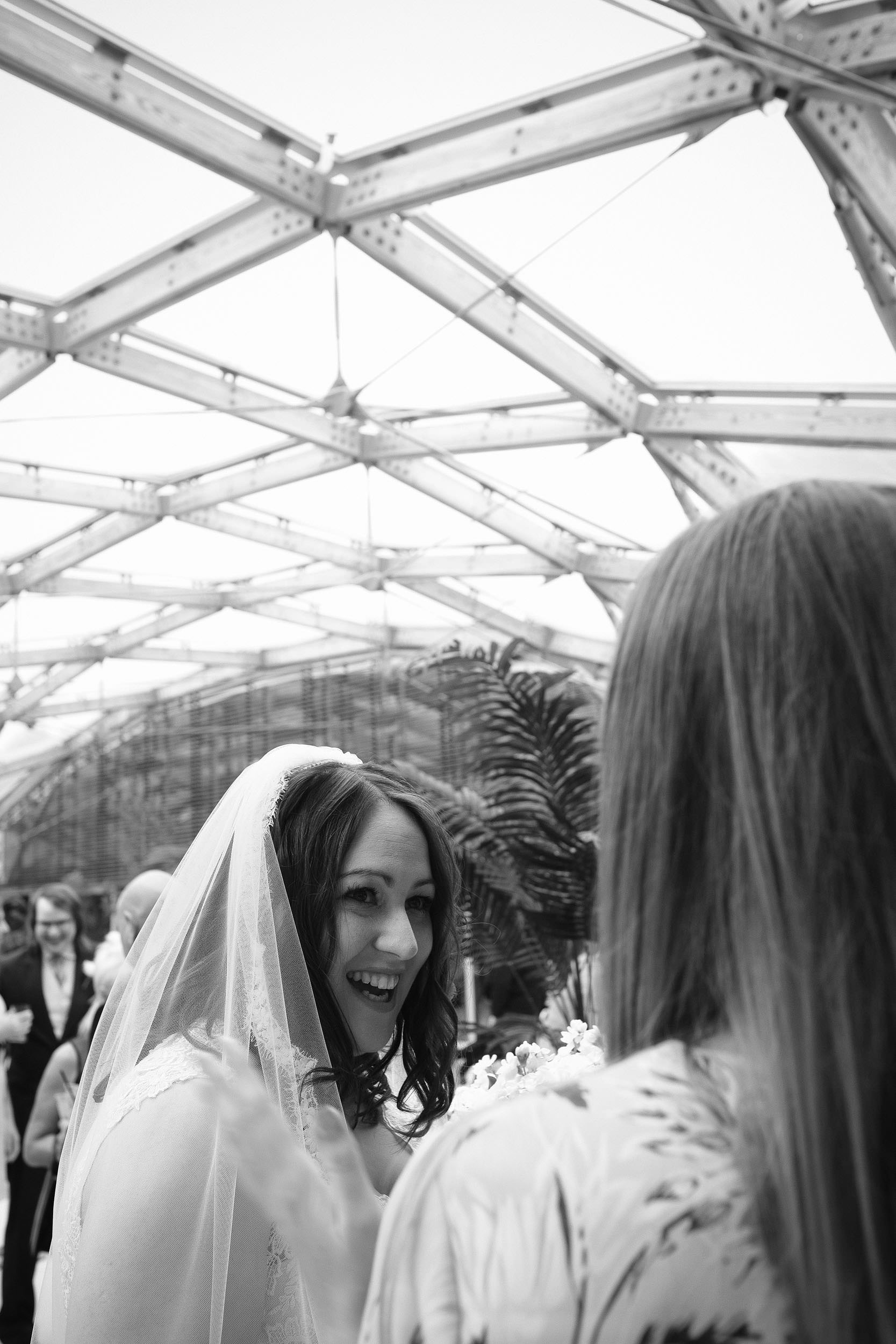 Black and white photo of bride laughing with wedding guests