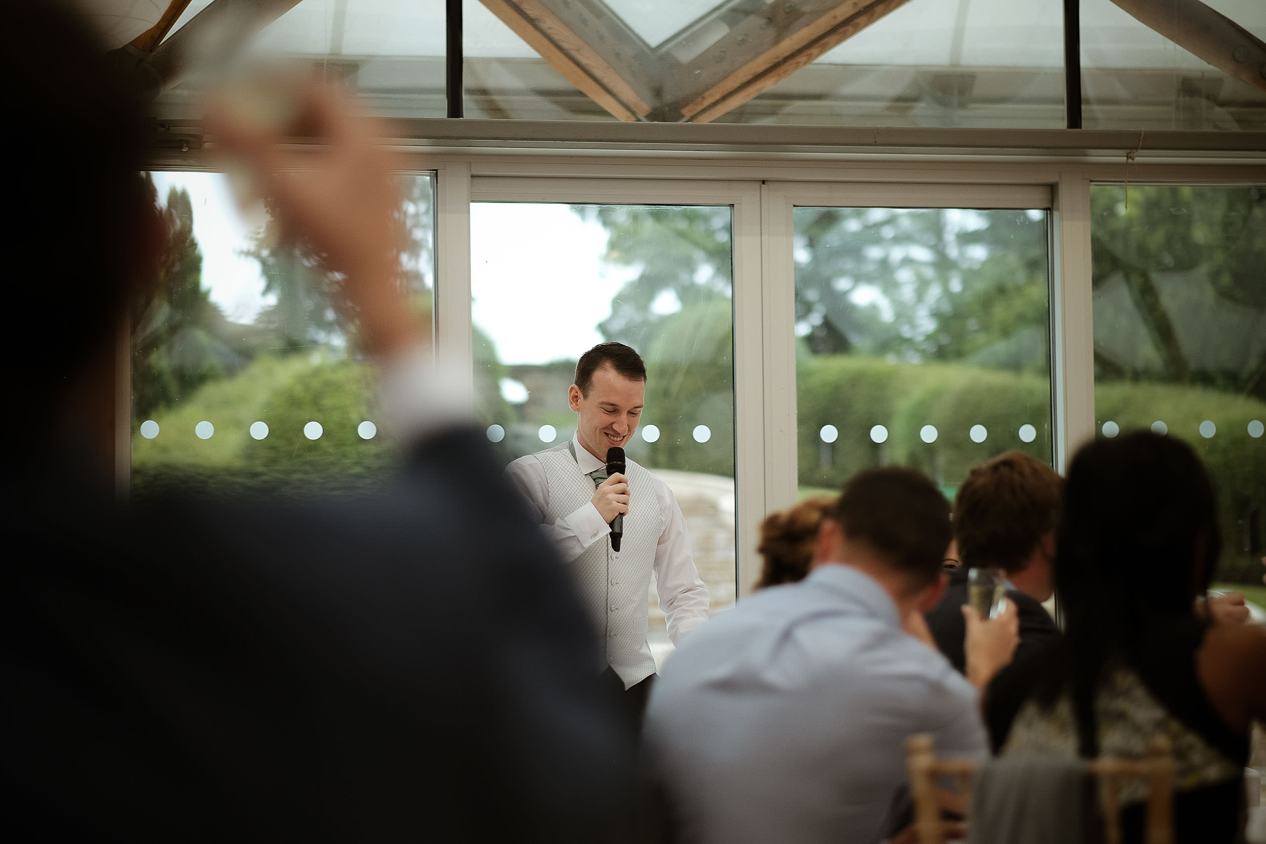 Groom giving wedding speech as guests watch