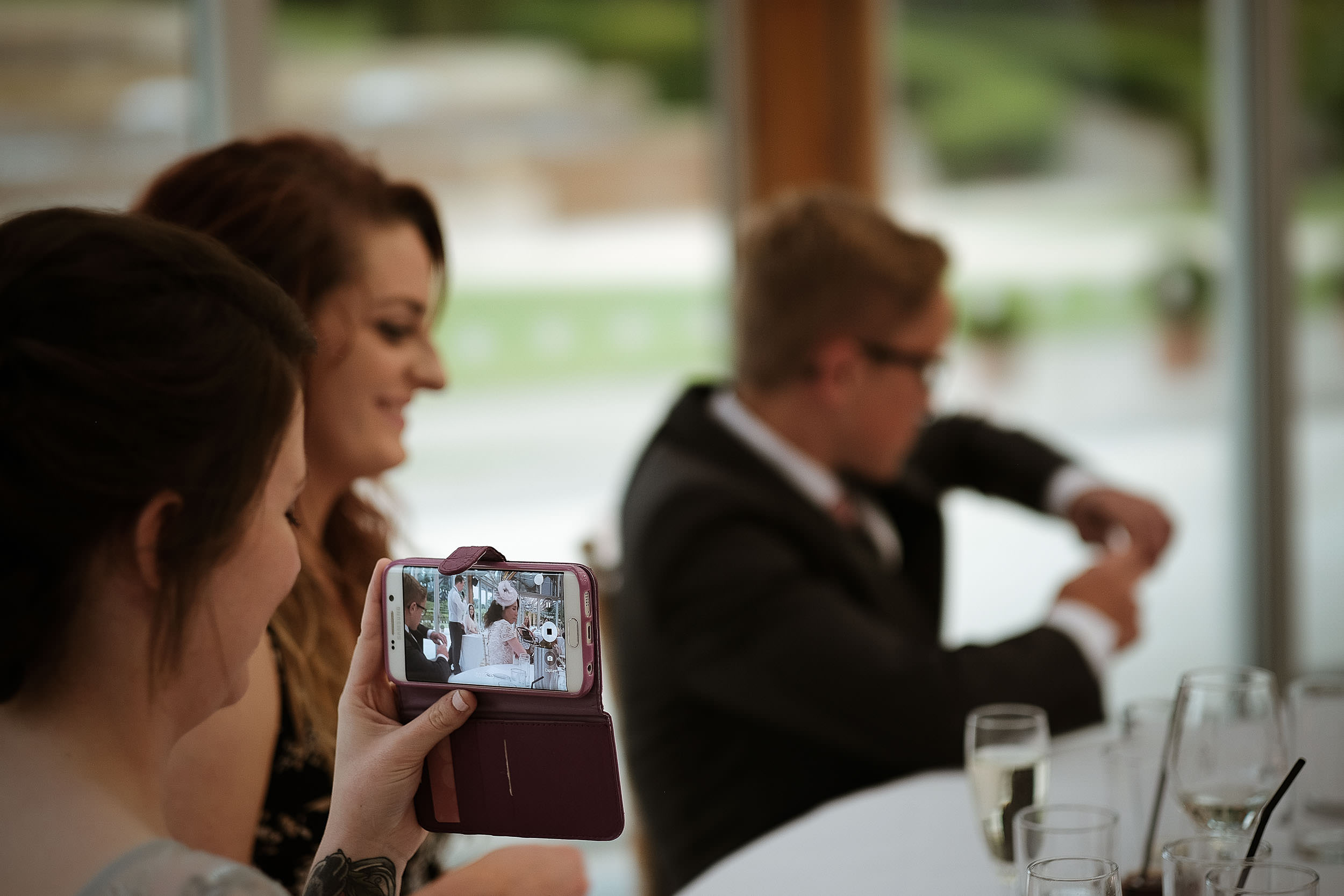 Guest photographing wedding speeches at the Alnwick Garden