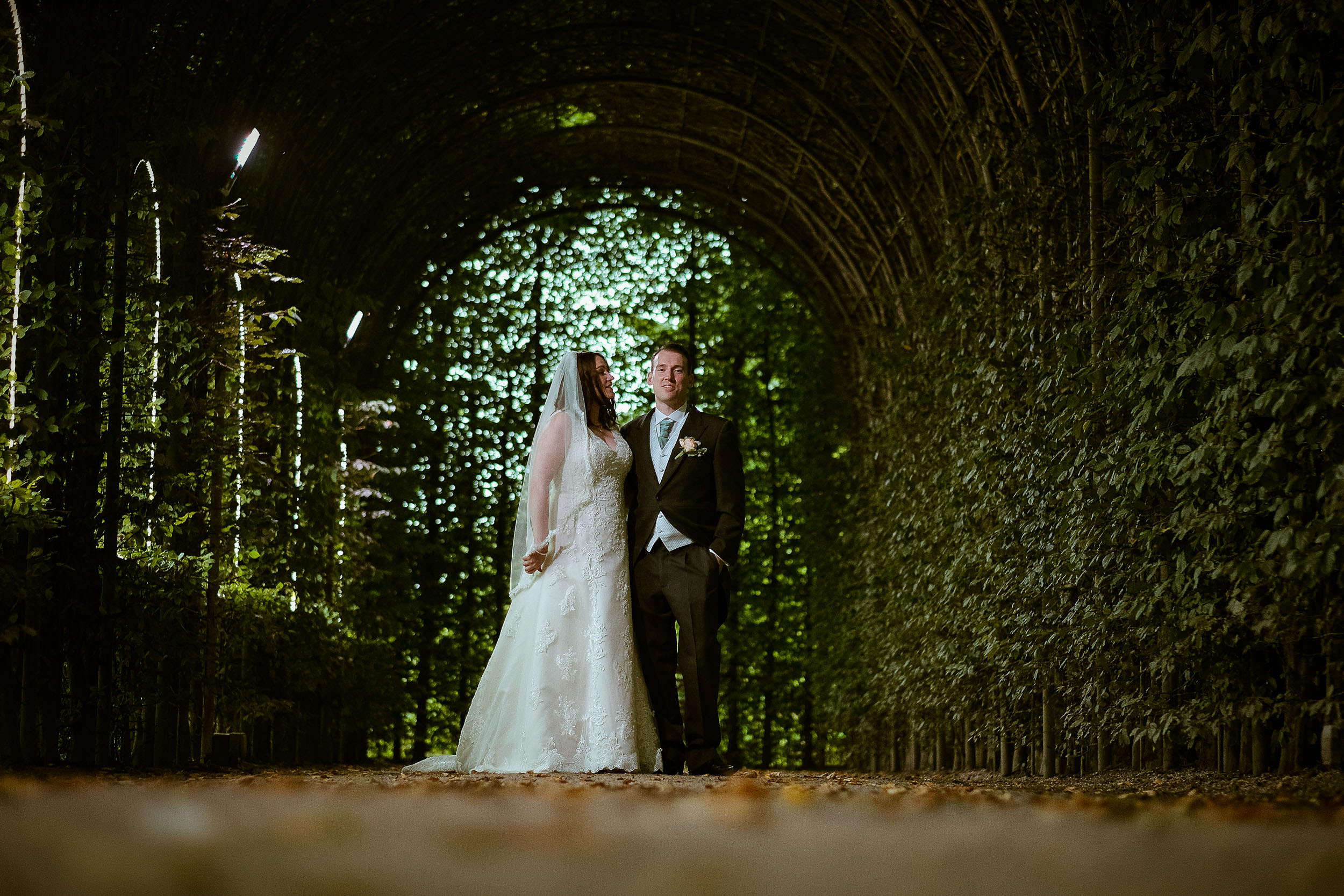 Bride and groom pose under vegetation arches