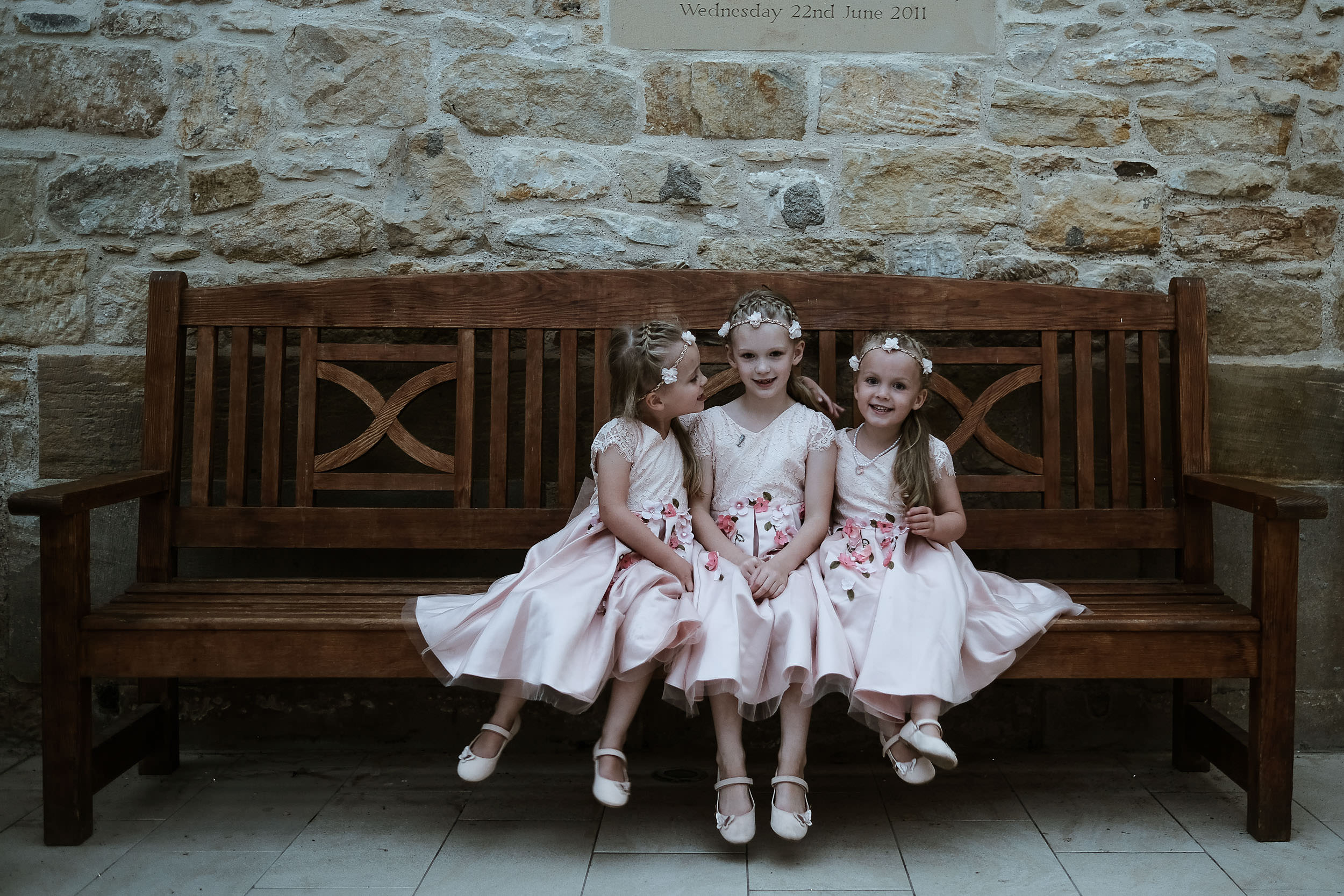 3 flower girls sitting on bench
