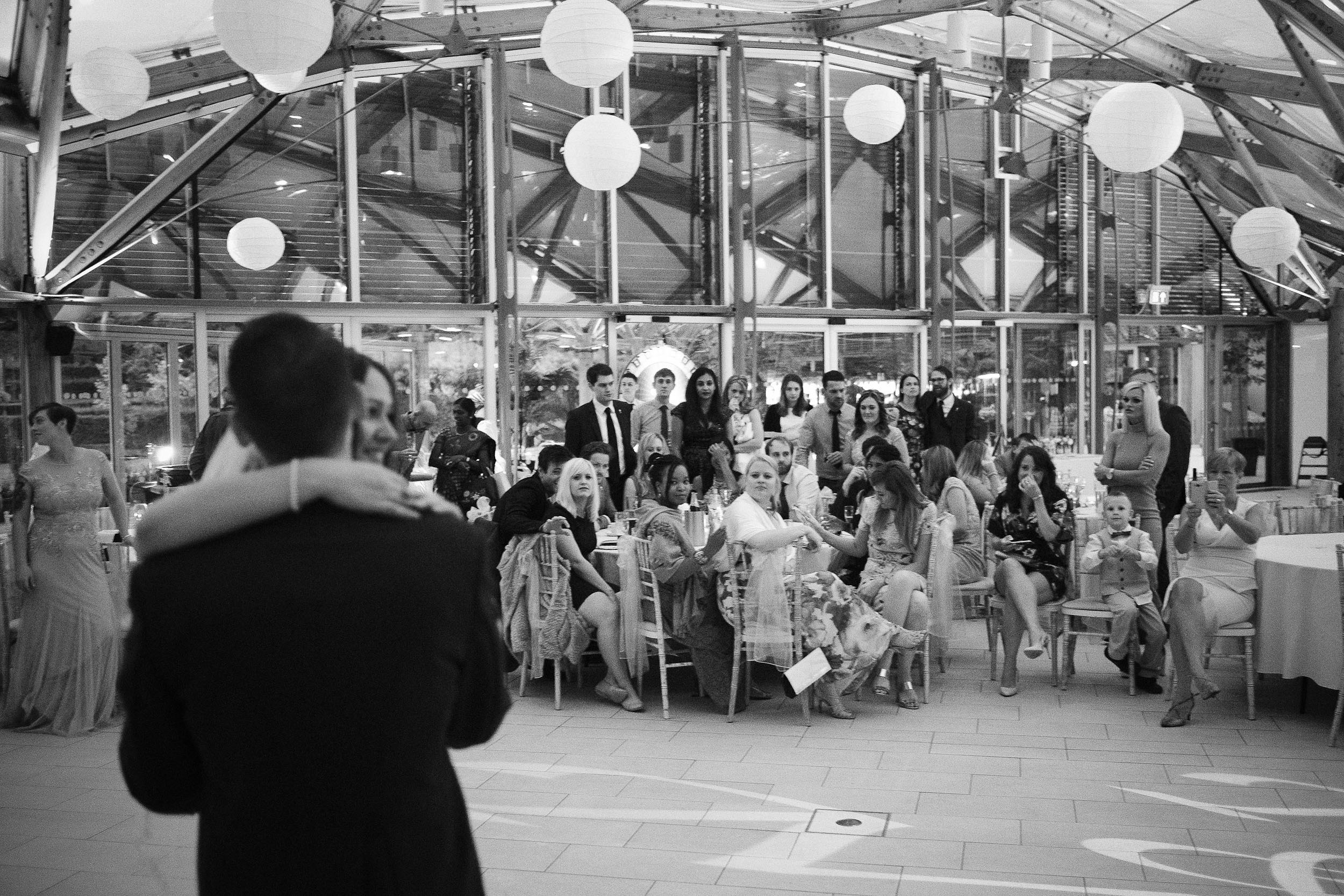 Black and white photo of first dance with guests watching