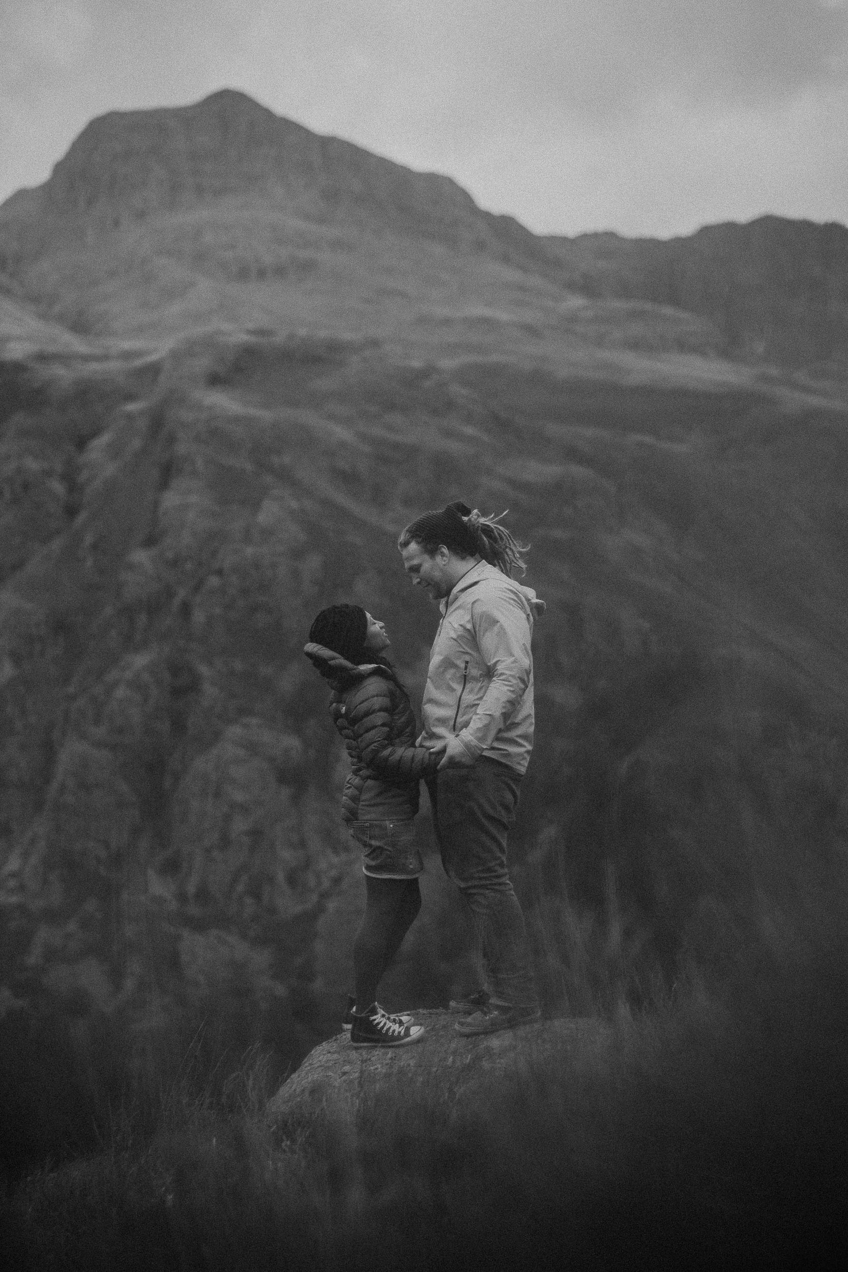 Black and white photo of engaged couple standing on rock