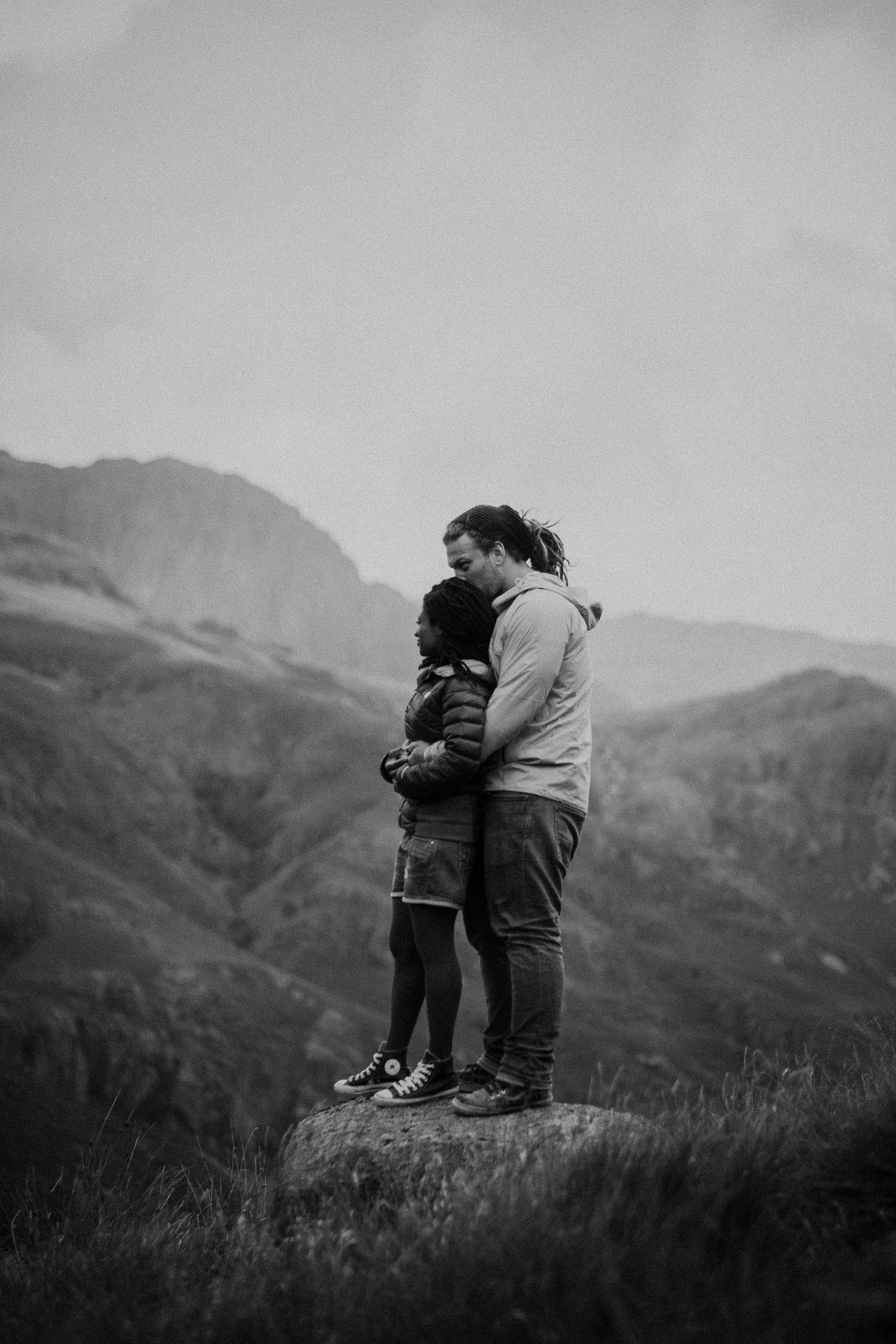 Black and white photo of pre-wedding couple cuddling on rock