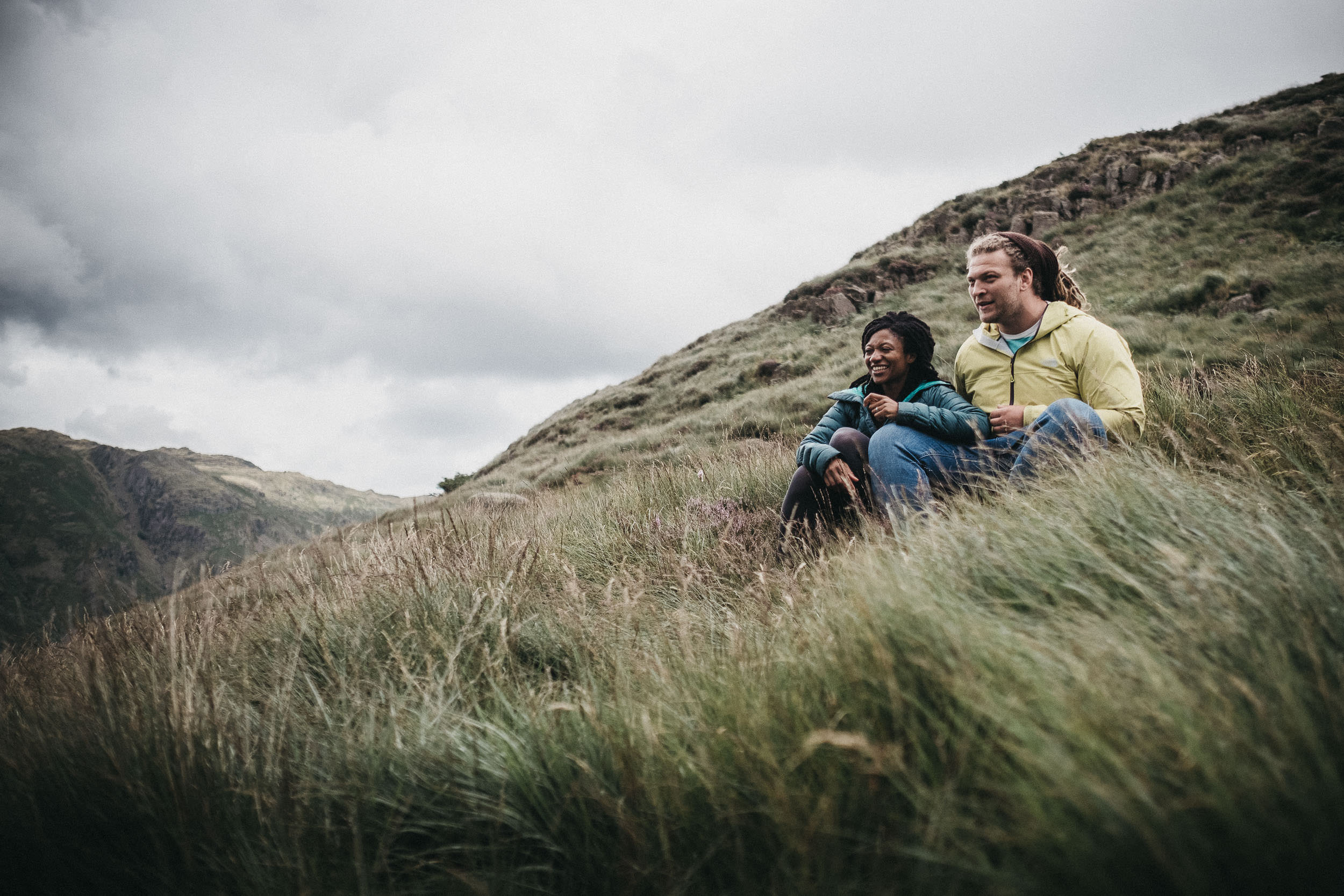 Couple laughing while sitting on Lake District hillside