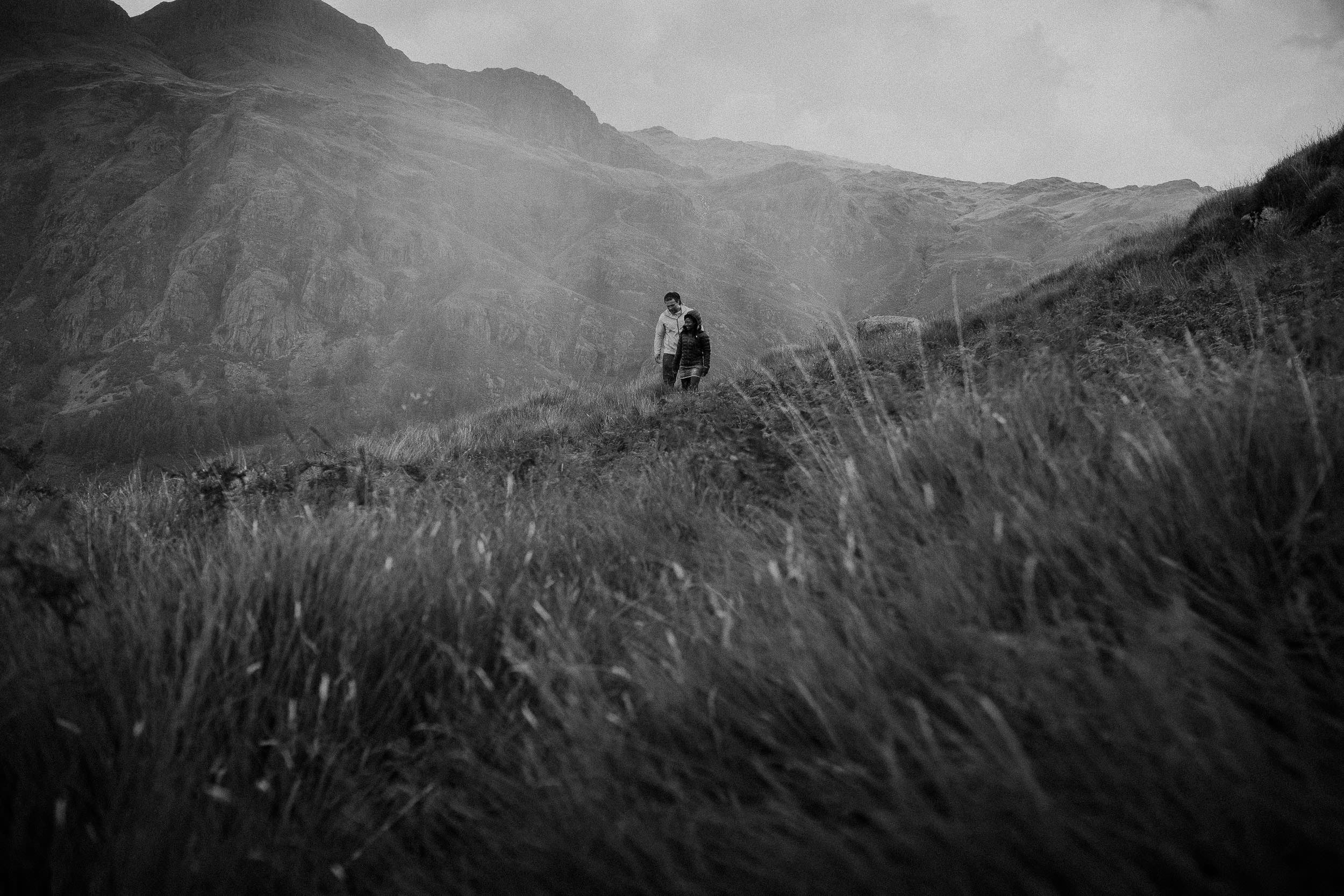 Black and white photo of couple in rain in Lake District hills