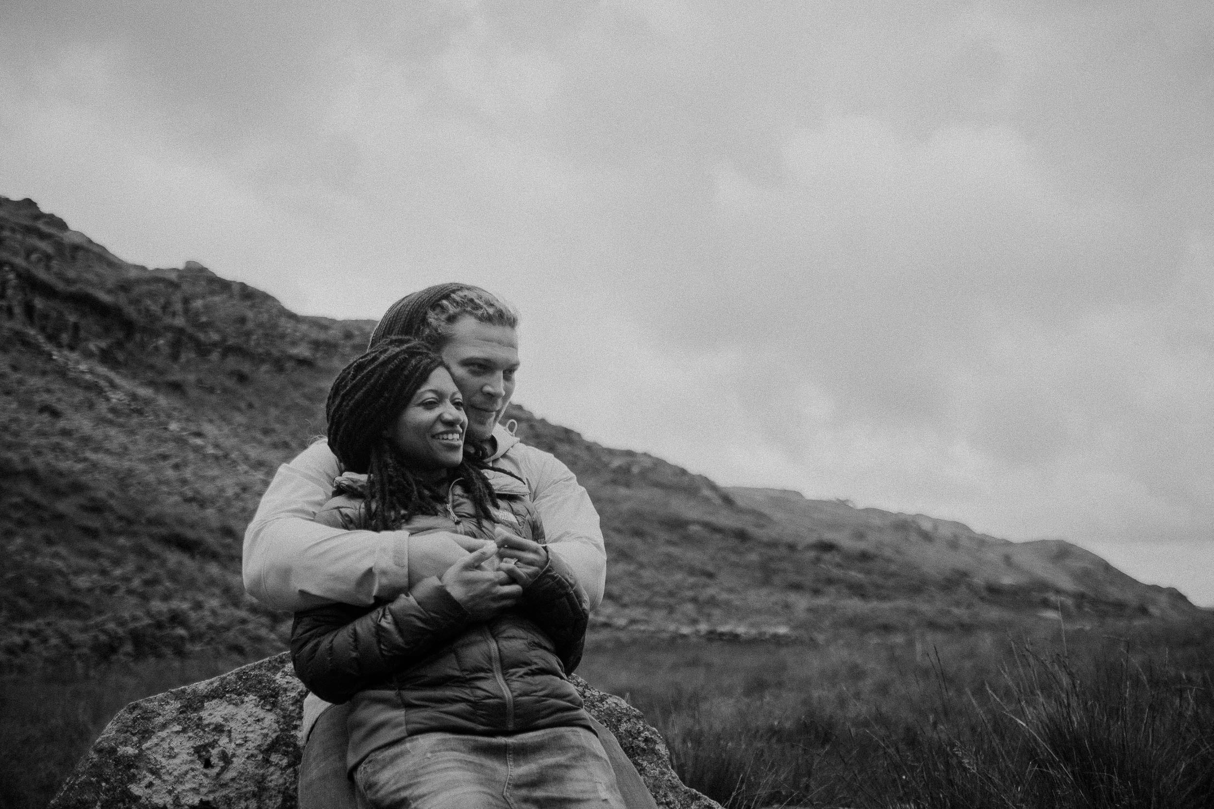 Black and white photo of couple cuddling and laughing with hills behind