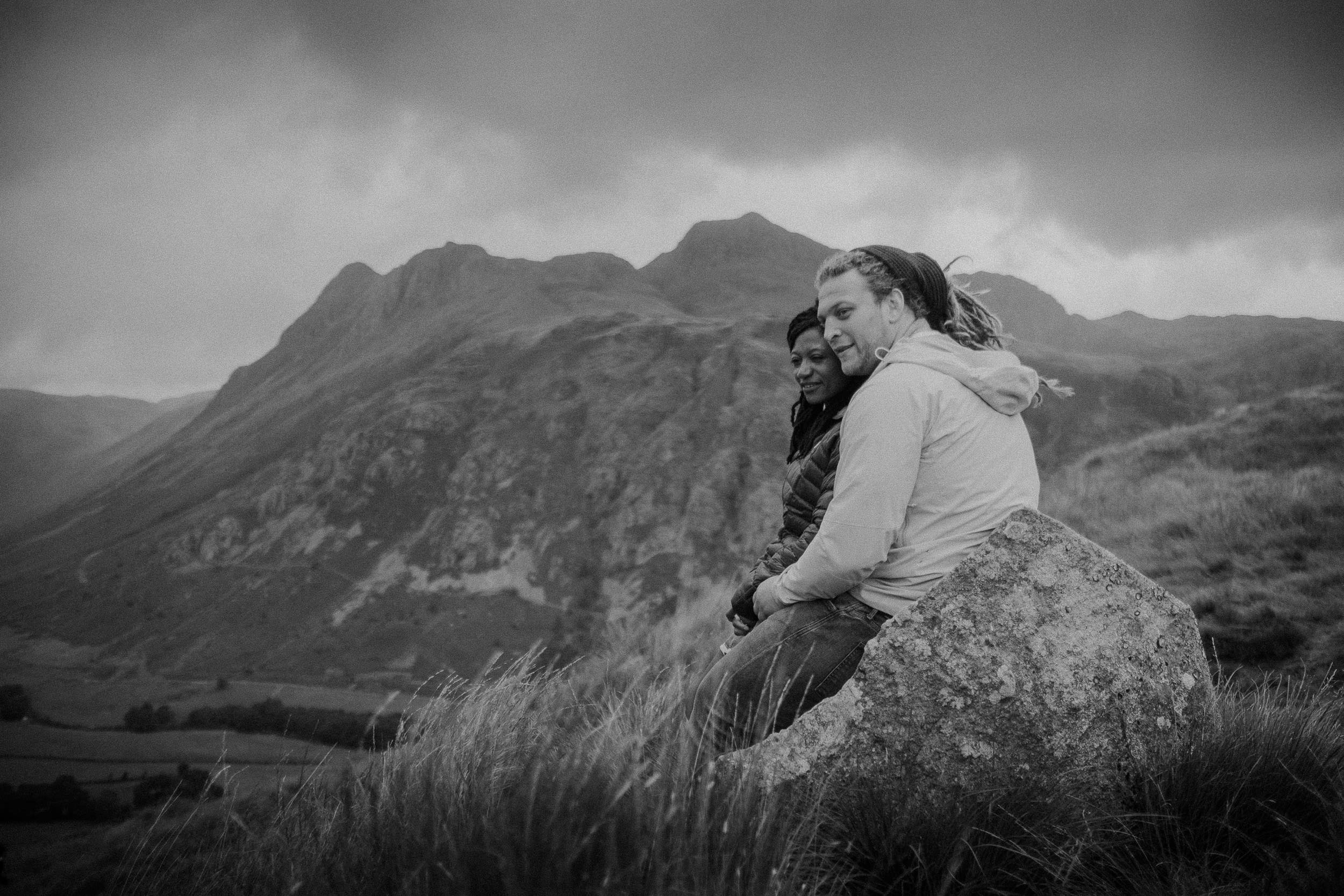 Black and white photo of couple sat on a rock looking out over the Lake District