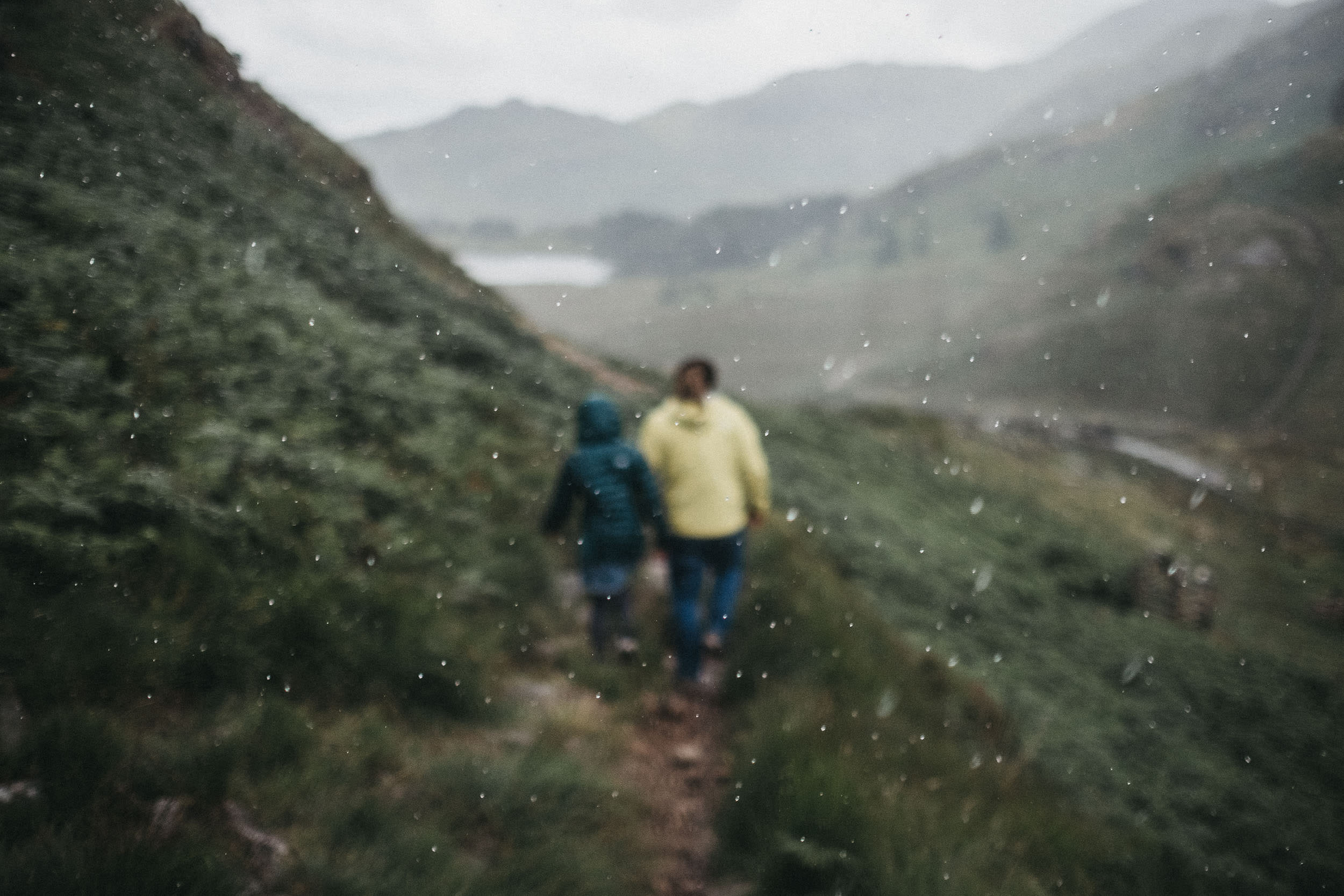 The rain pours down in the Lake District while an engaged couple walks down a fell trail