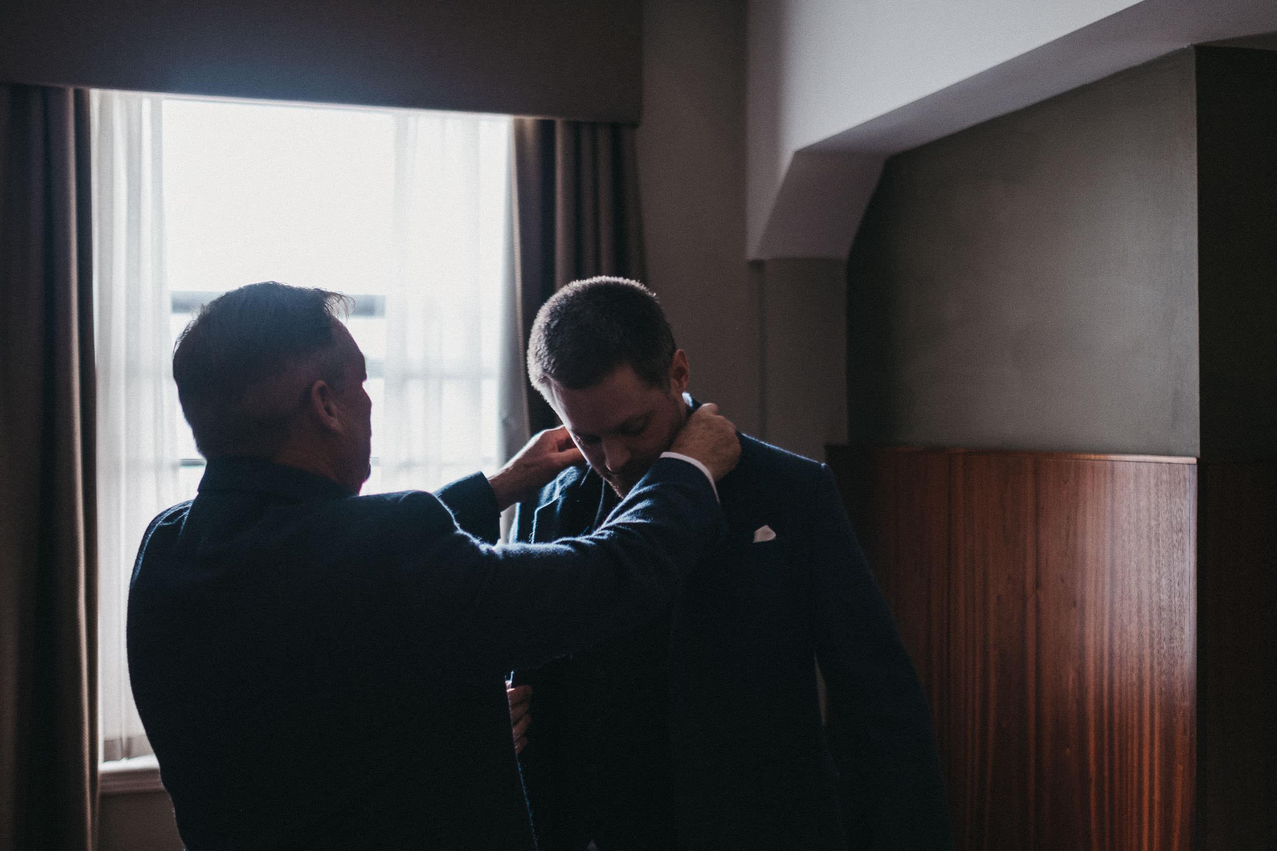 Father of groom adjusting groom's jacket