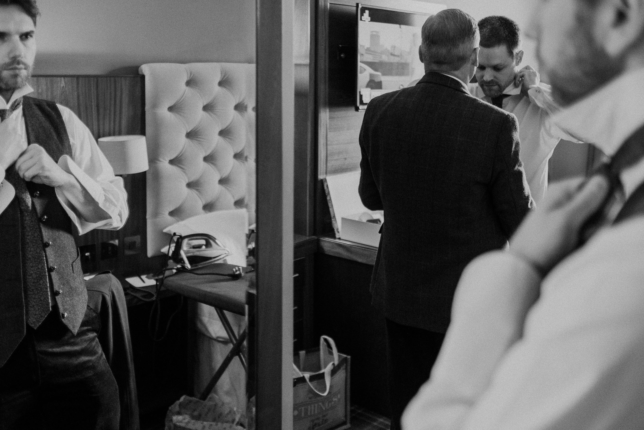 Black and white photo of groom and best man getting ready