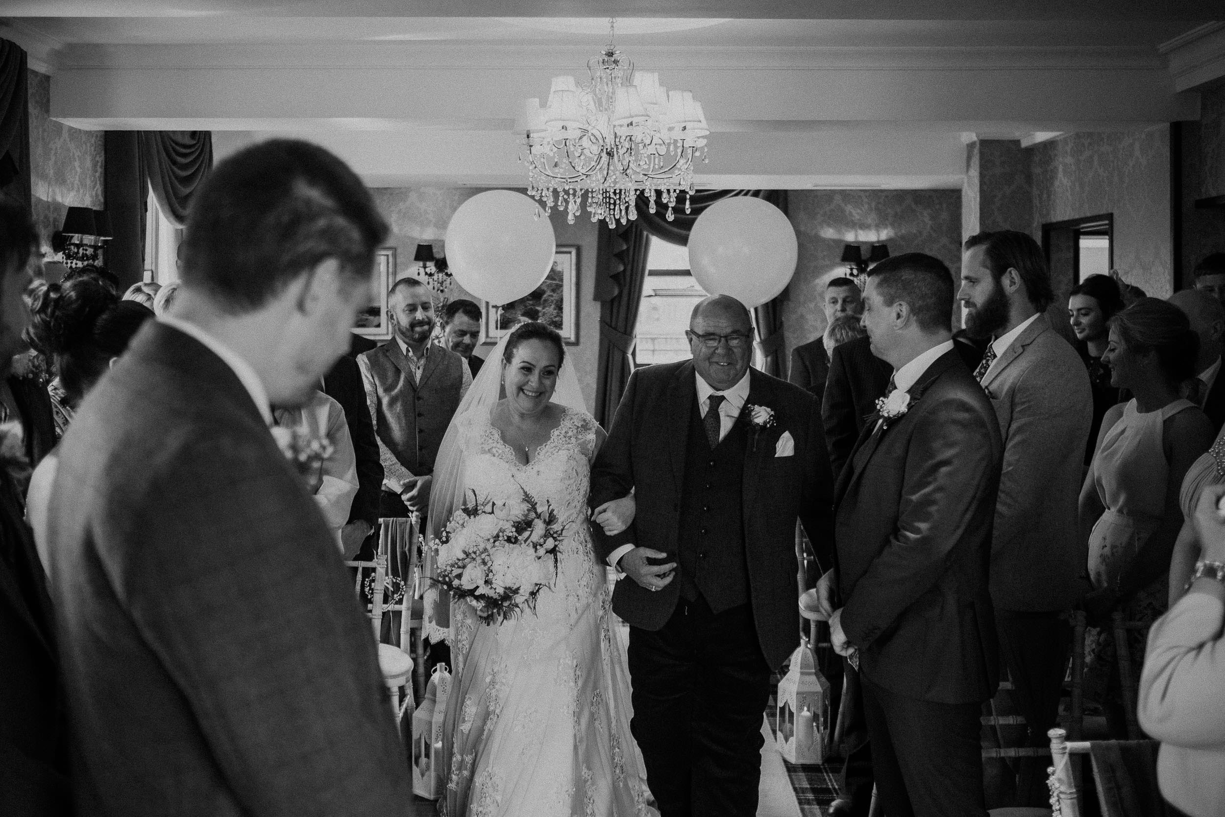 Black and white photo of bride being walked down the aisle by her father