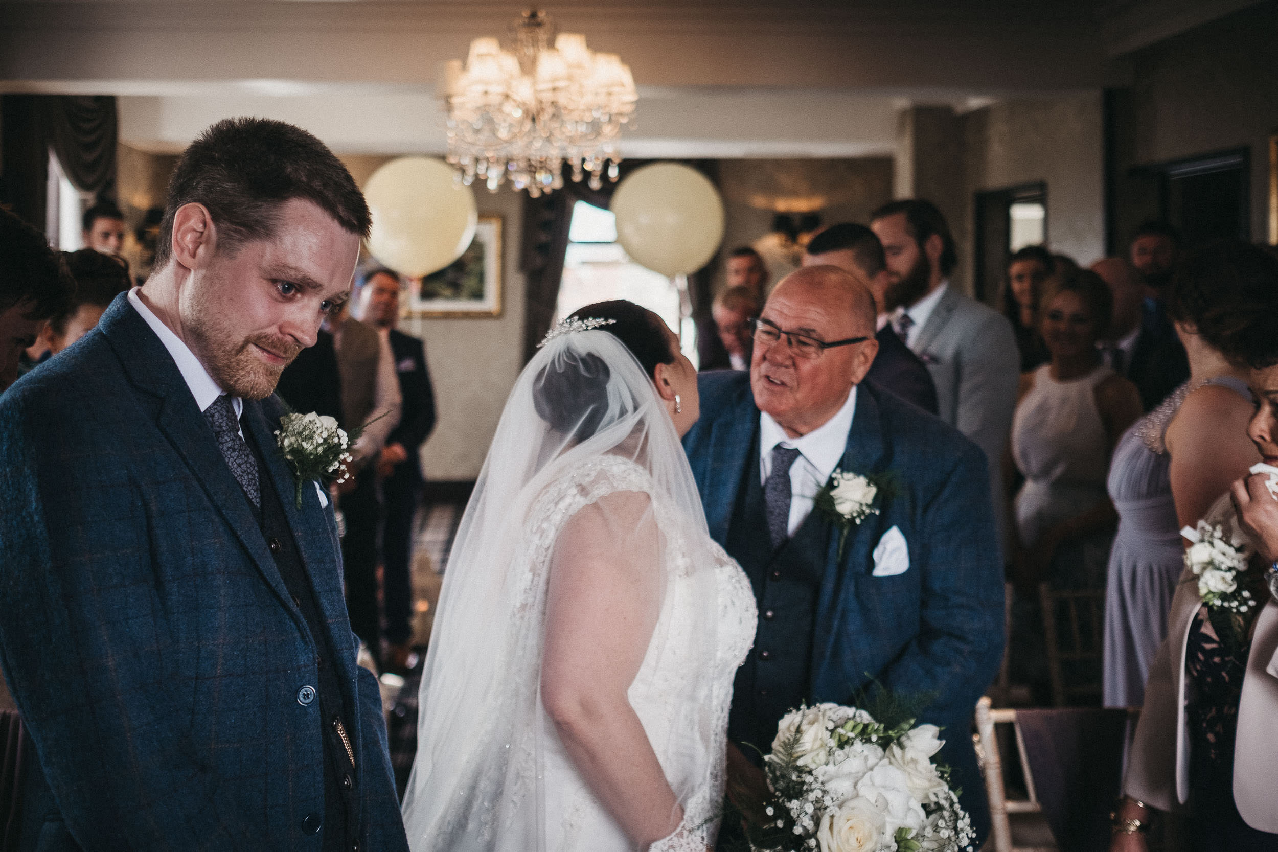 Bride kissing her father while the nervous groom waits at the end of the aisle
