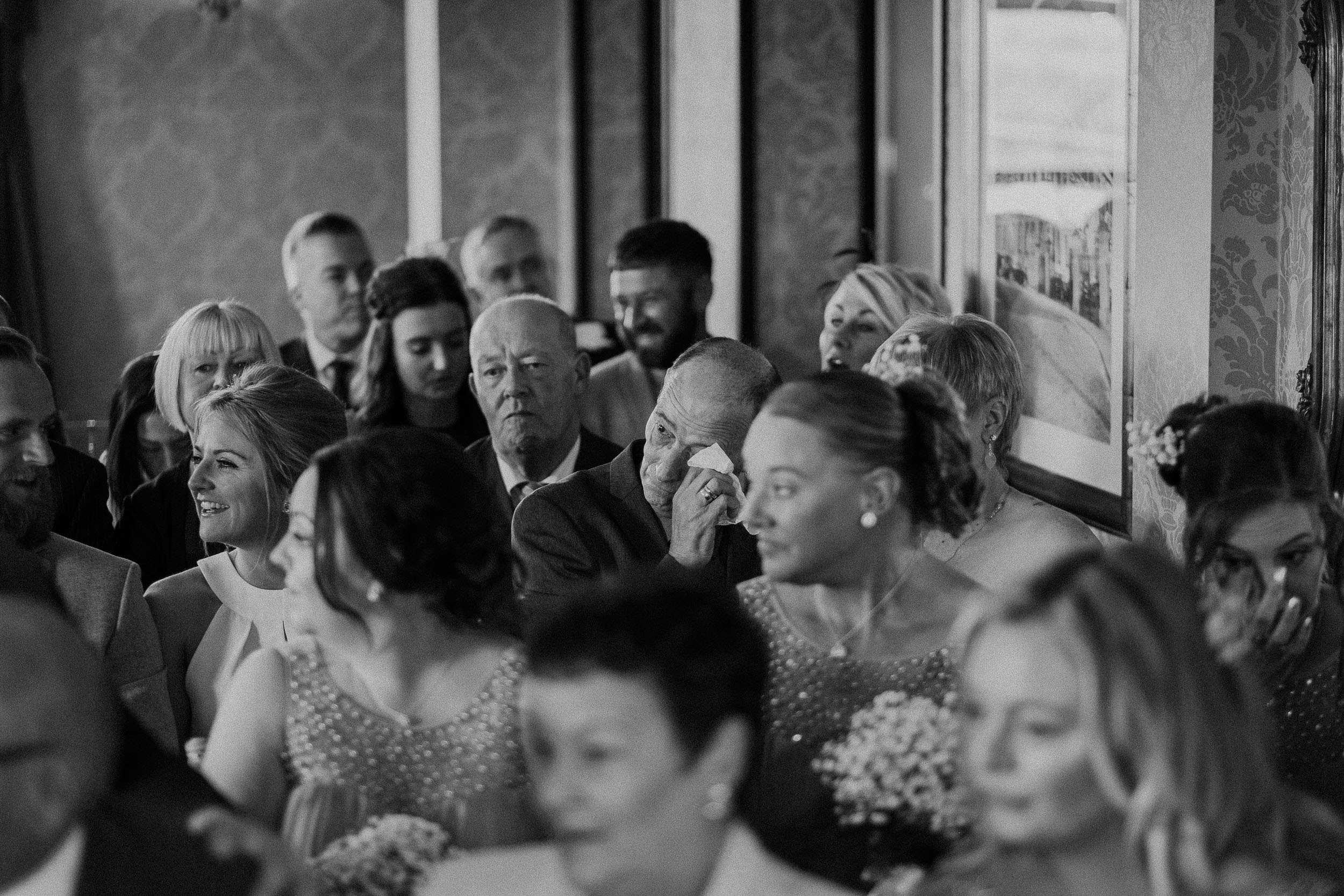 Black and white photo of guest crying during the wedding ceremony