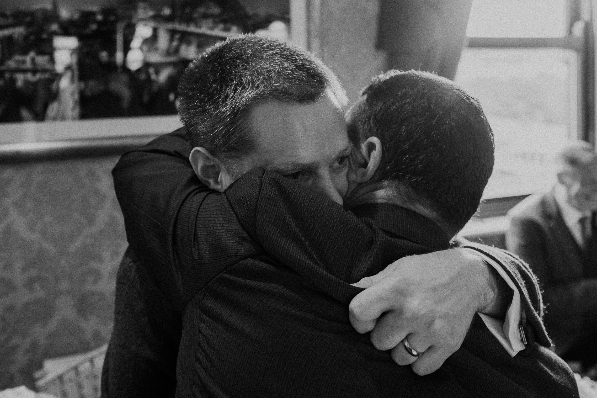 Black and white photo of guest hugging groom after the wedding ceremony