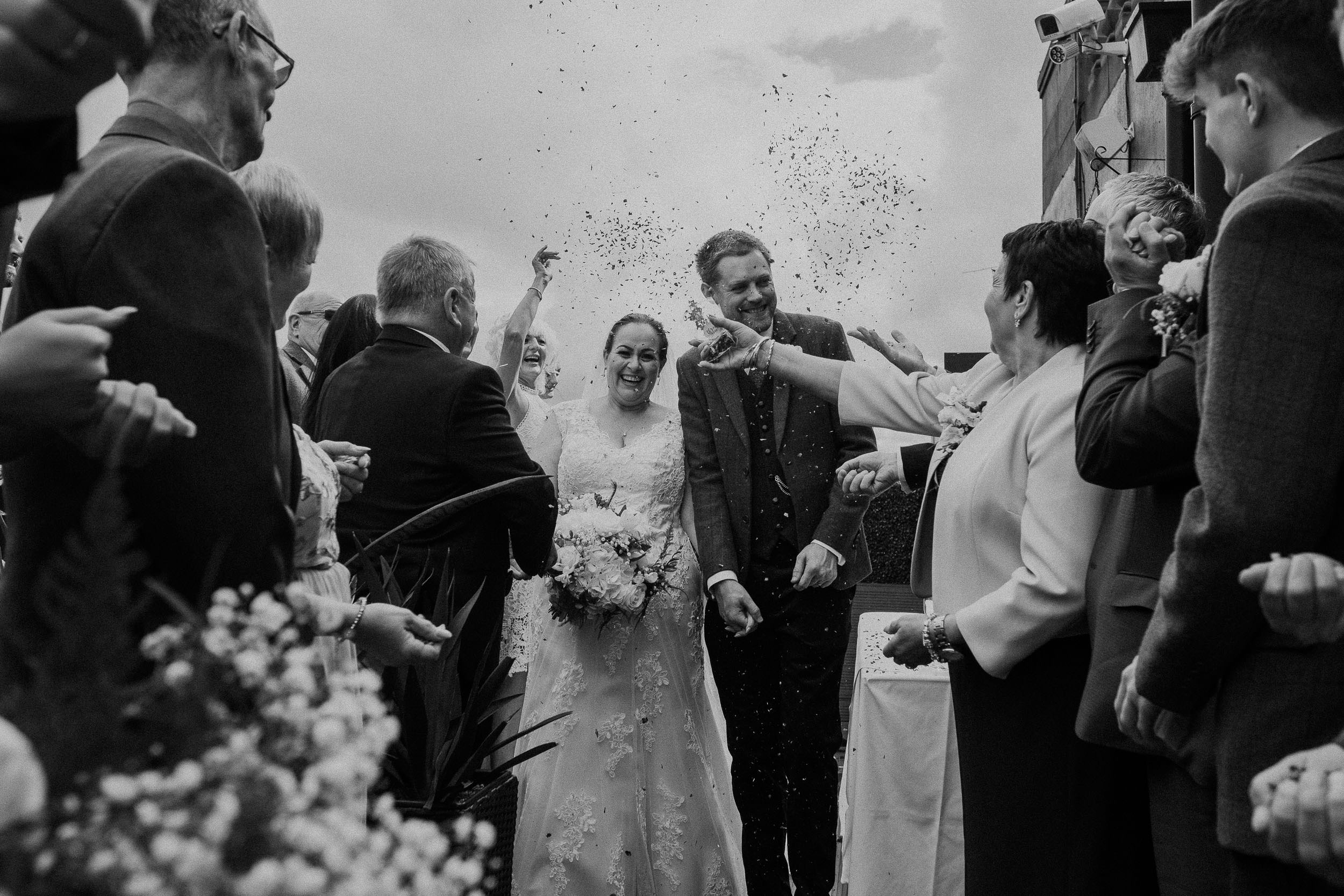 Black and white photo of the bride and groom being showered with confetti
