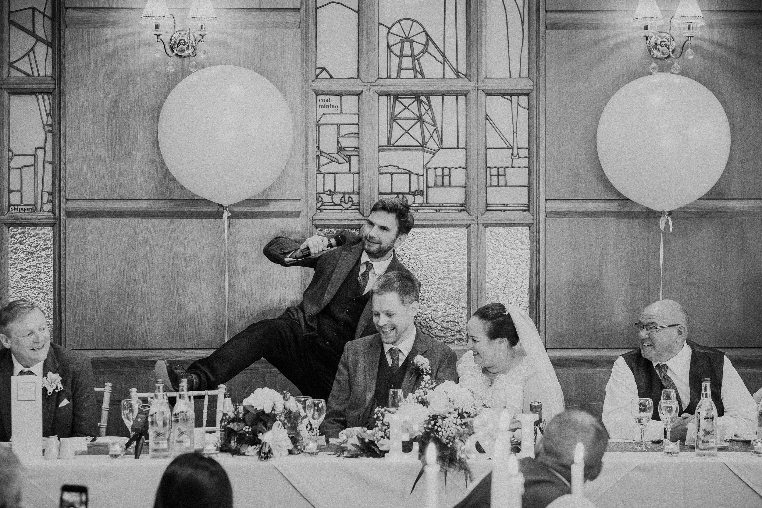 Black and white photo of best man's lifting his leg up during speech