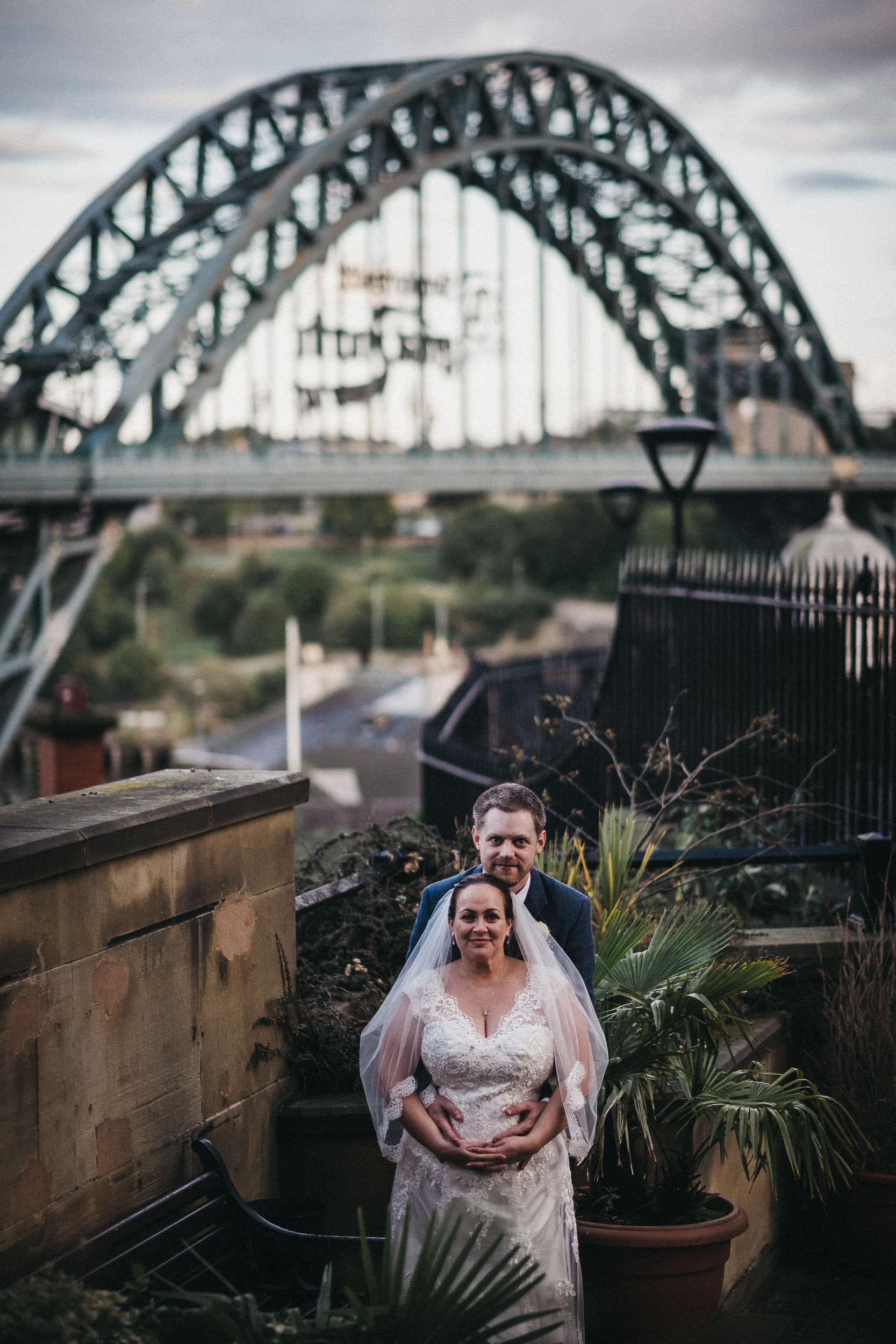 Bride and groom cuddling with Tyne Bride behind