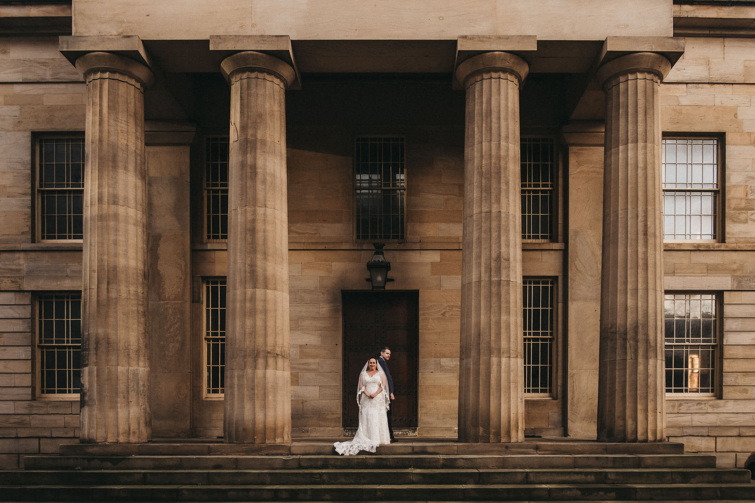Bride and groom posing on the steps of the Moot Hall