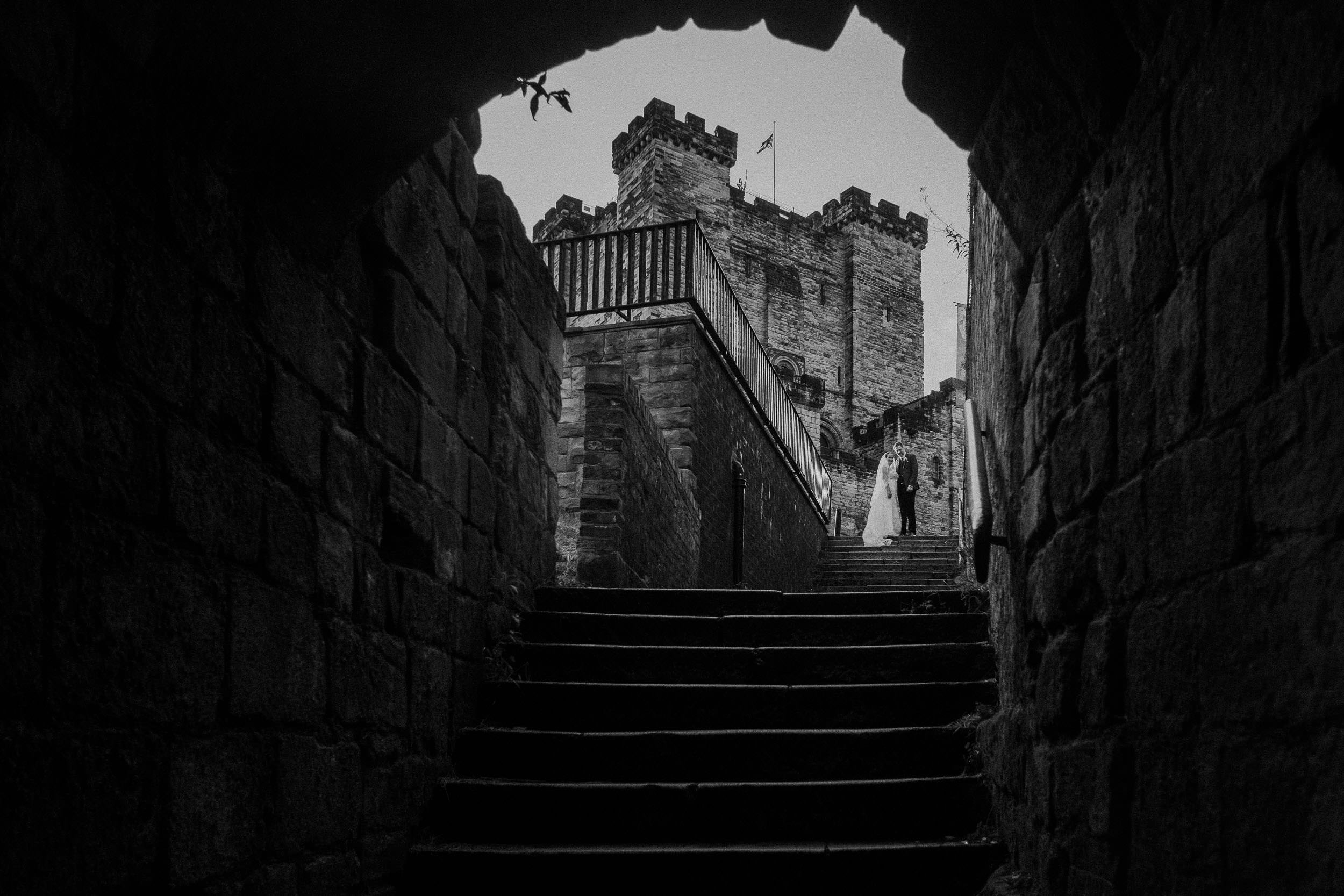 Black and white photo of bride and groom at top of steps with Newcastle Castle behind