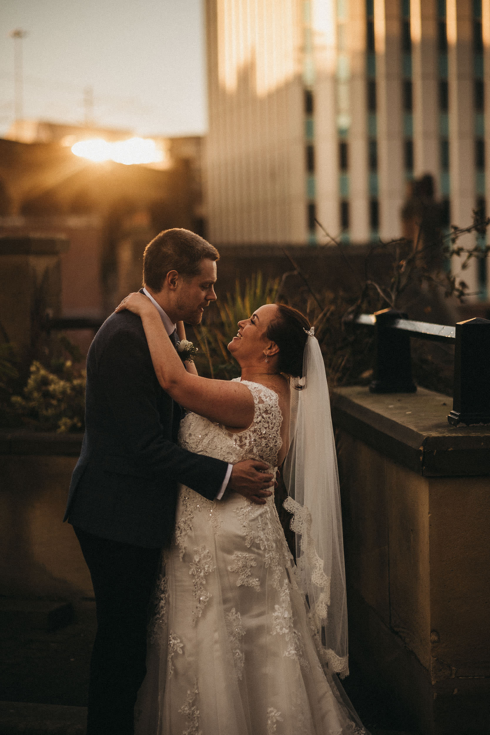 Bride and groom embrace with beautiful sunlight behind