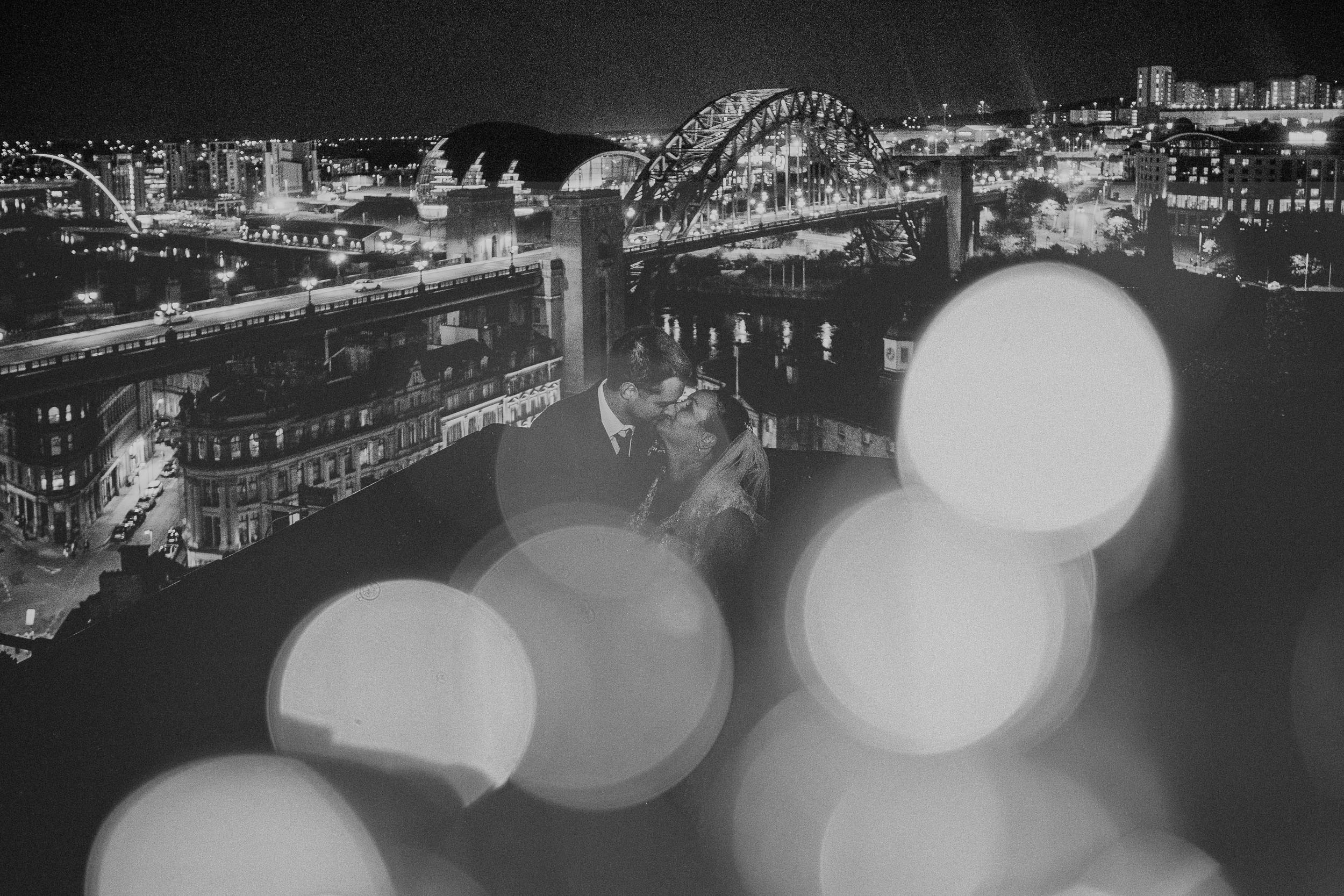 Black and white photo of bride and groom kissing with Newcastle skyline behind and sparkling lights