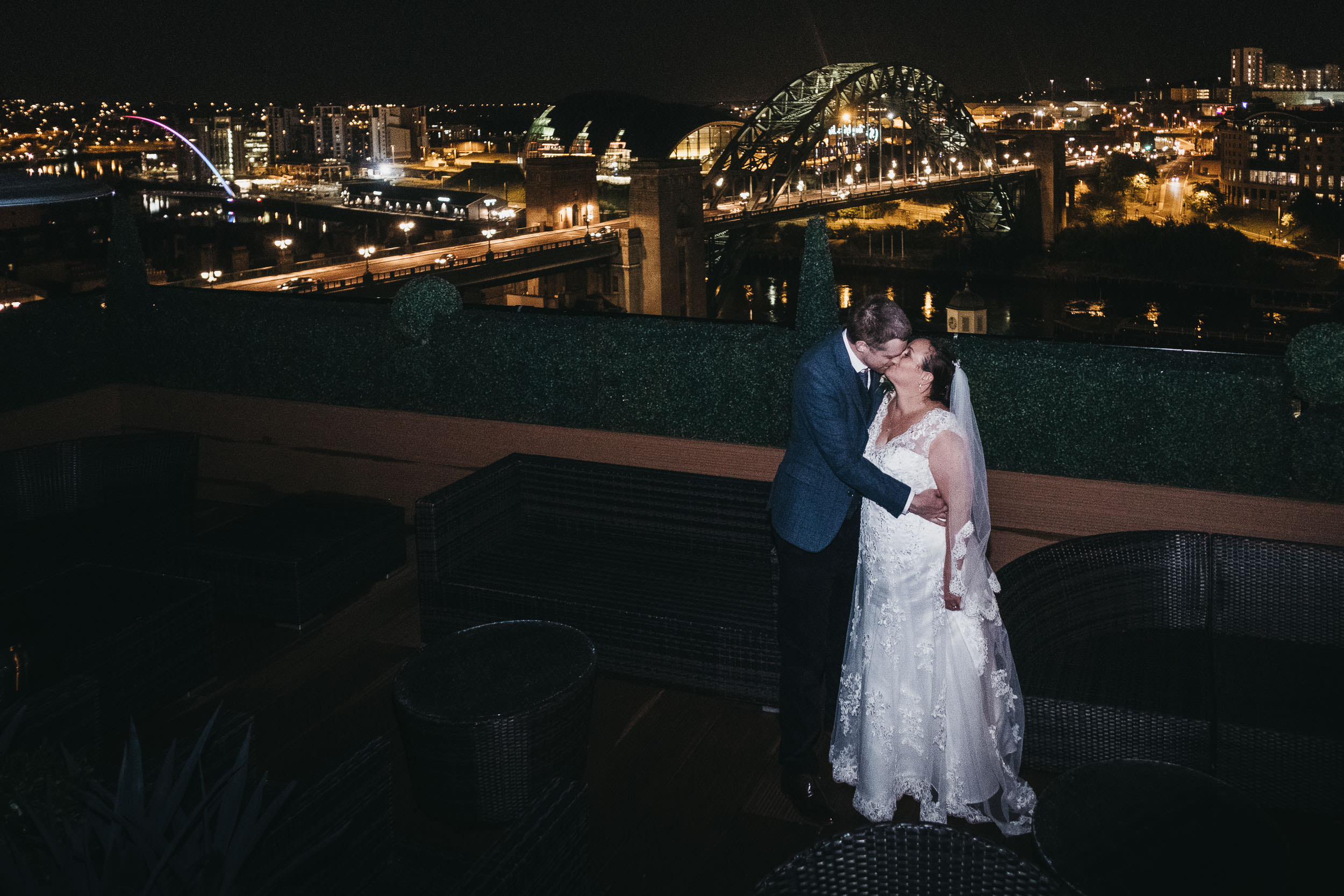 Bride and groom kissing at night on the rooftop of the Vermont Hotel