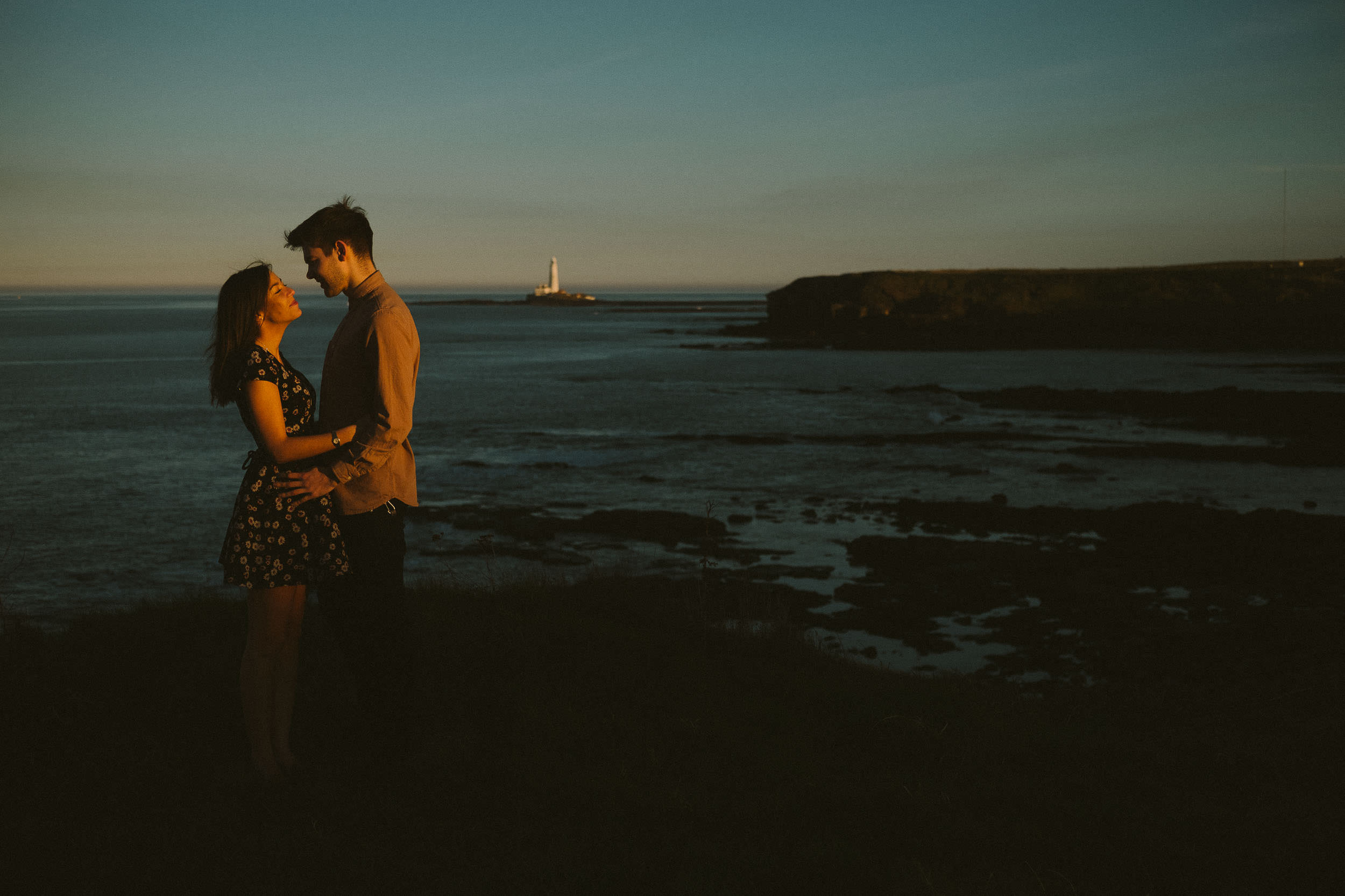 Couple bathed in warm light on cliffs above the North Sea