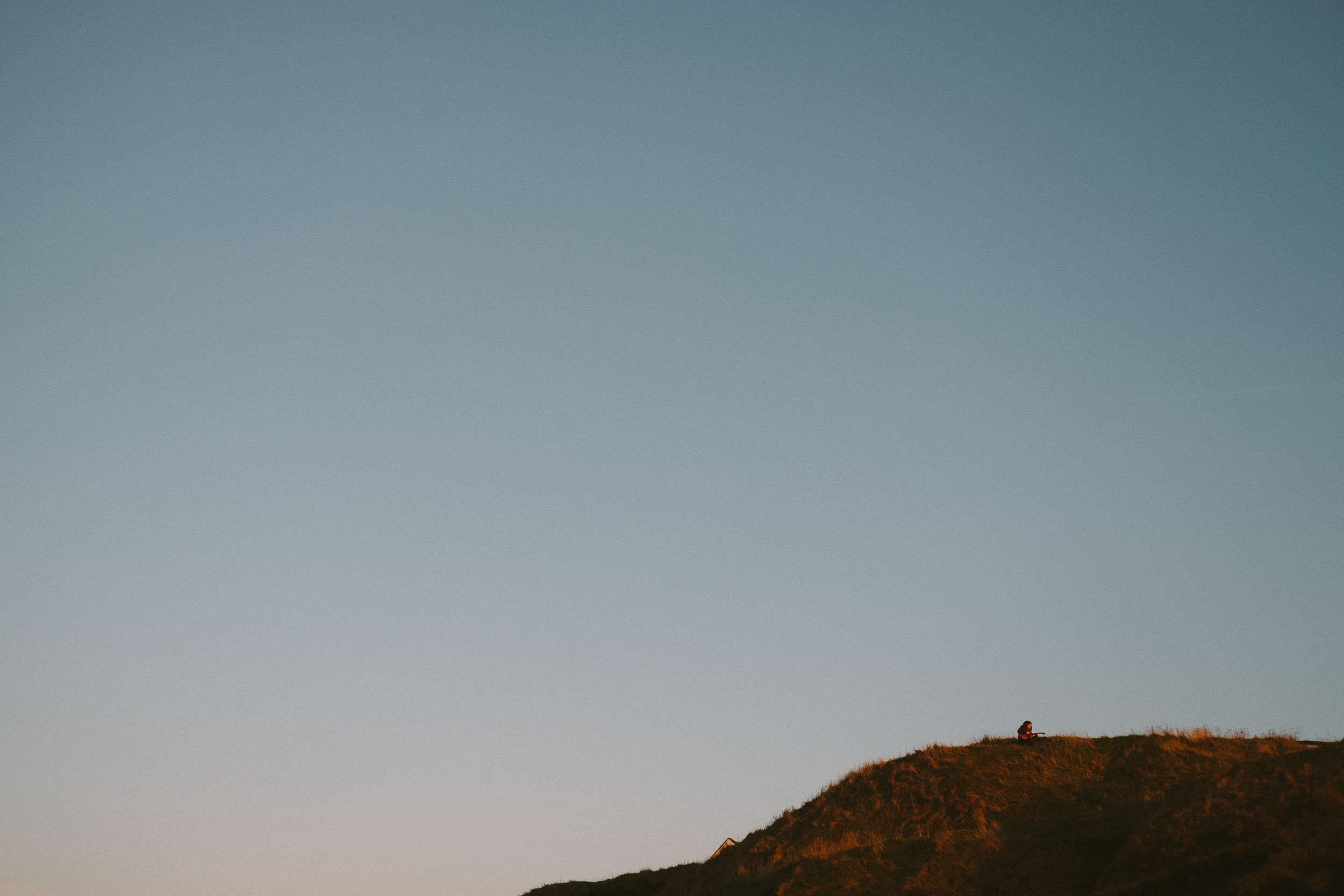 Girl playing guitar on clifftop on Northumberland coast