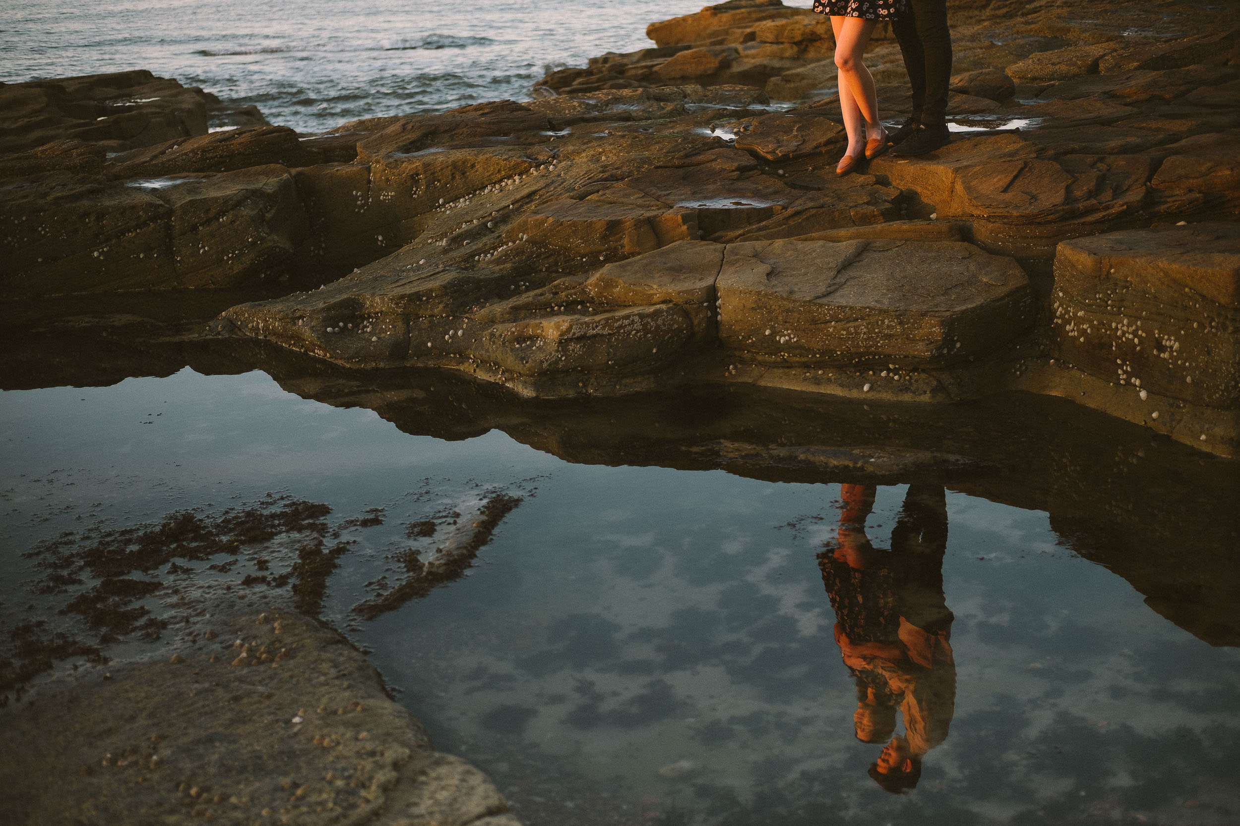 Cuddling couple reflected in rock pool