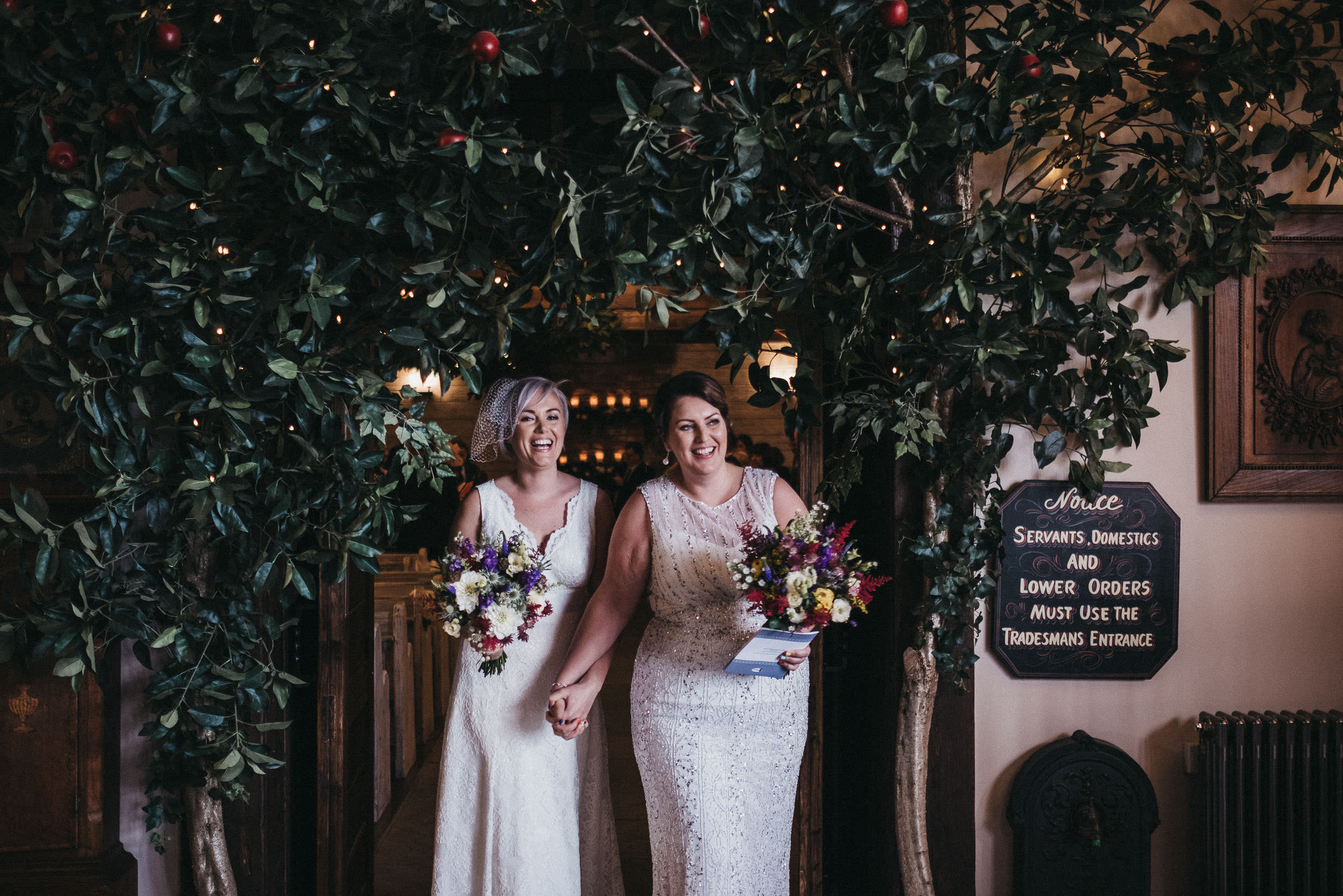 BTwo brides emerge smiling from their wedding ceremony