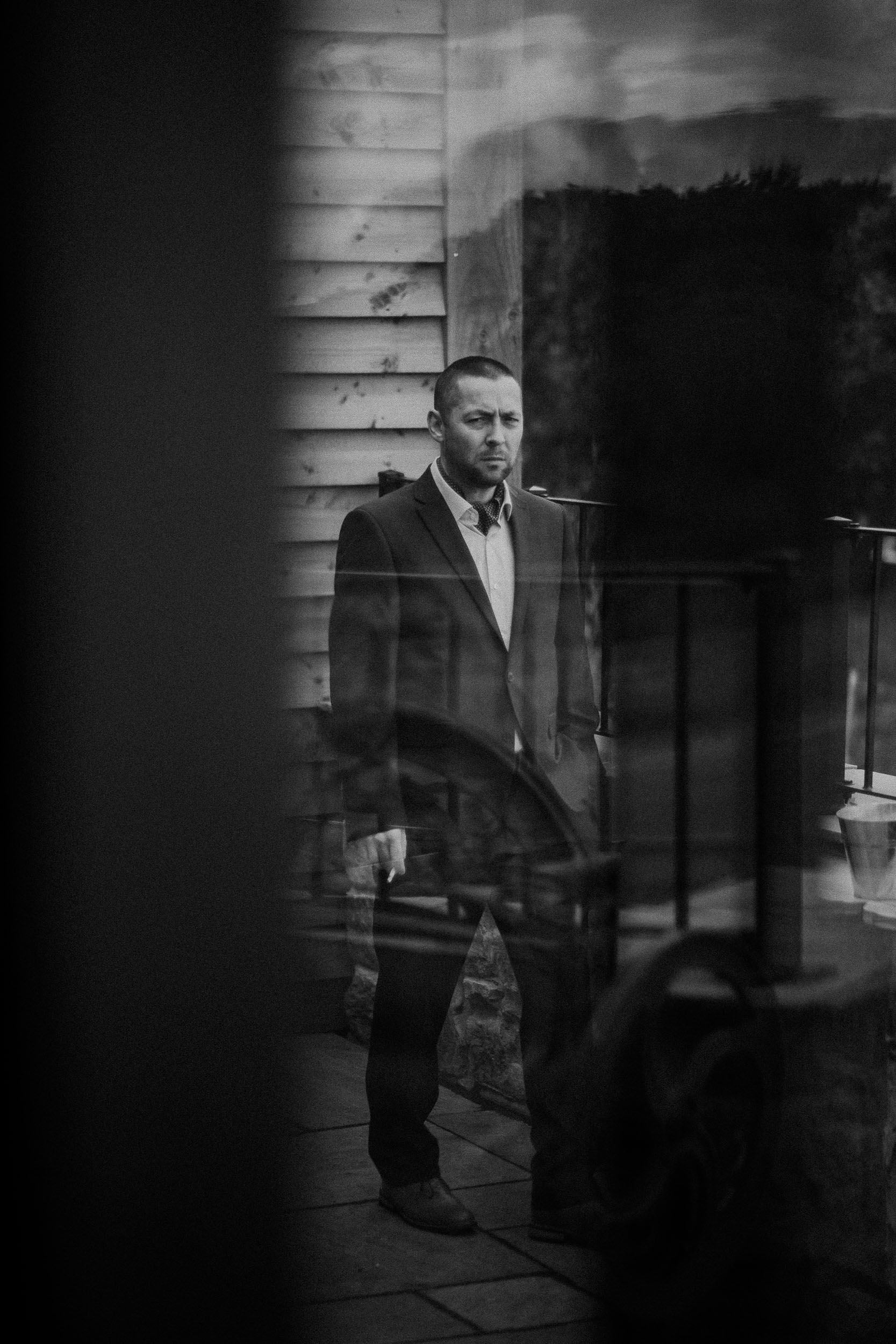 Black and white photo of guest smoking at wedding