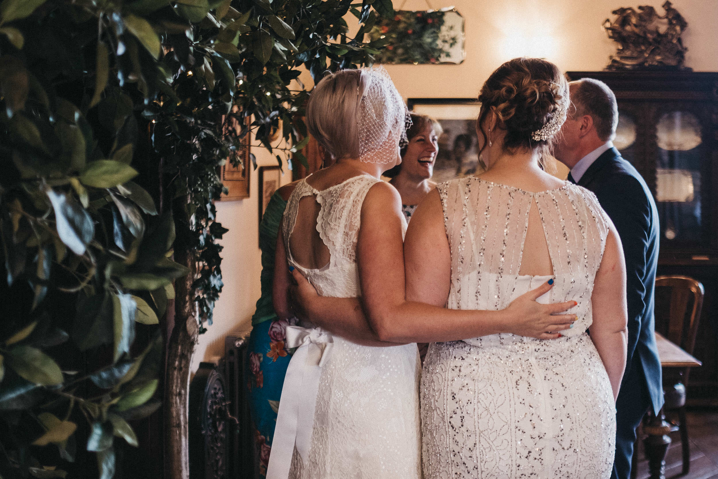 Brides hold each others backs during wedding reception