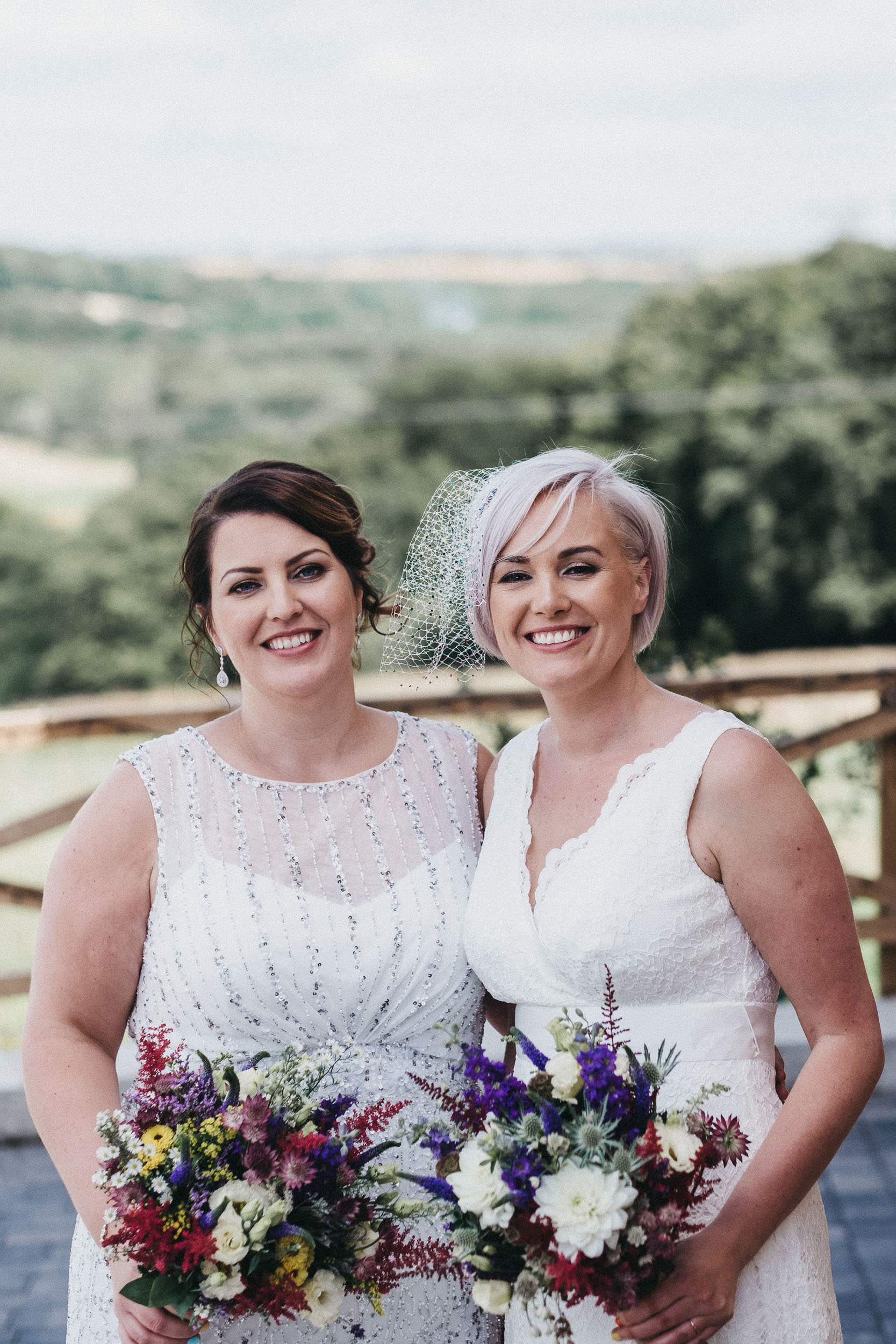 Two brides smiling while holding bouquets at same sex wedding