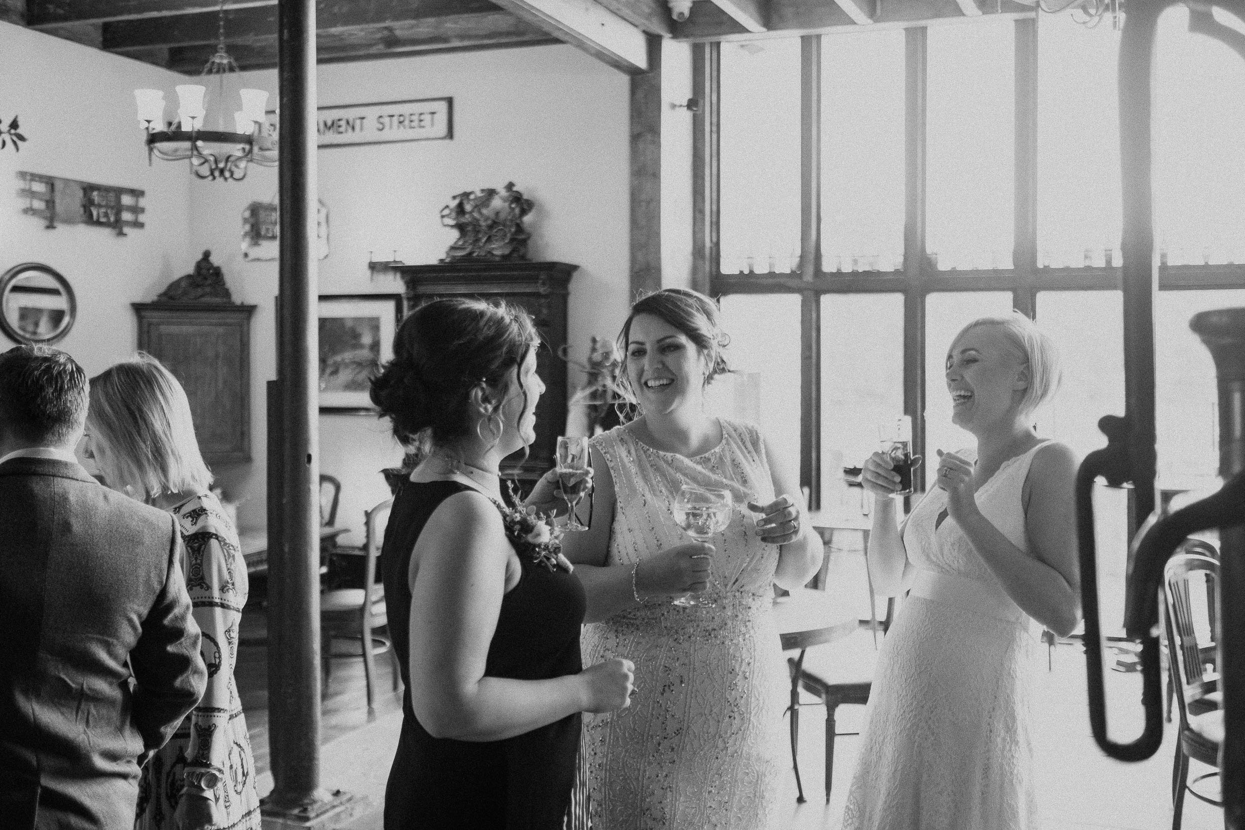 Black and white photo of brides laughing with guests at South Causey Inn