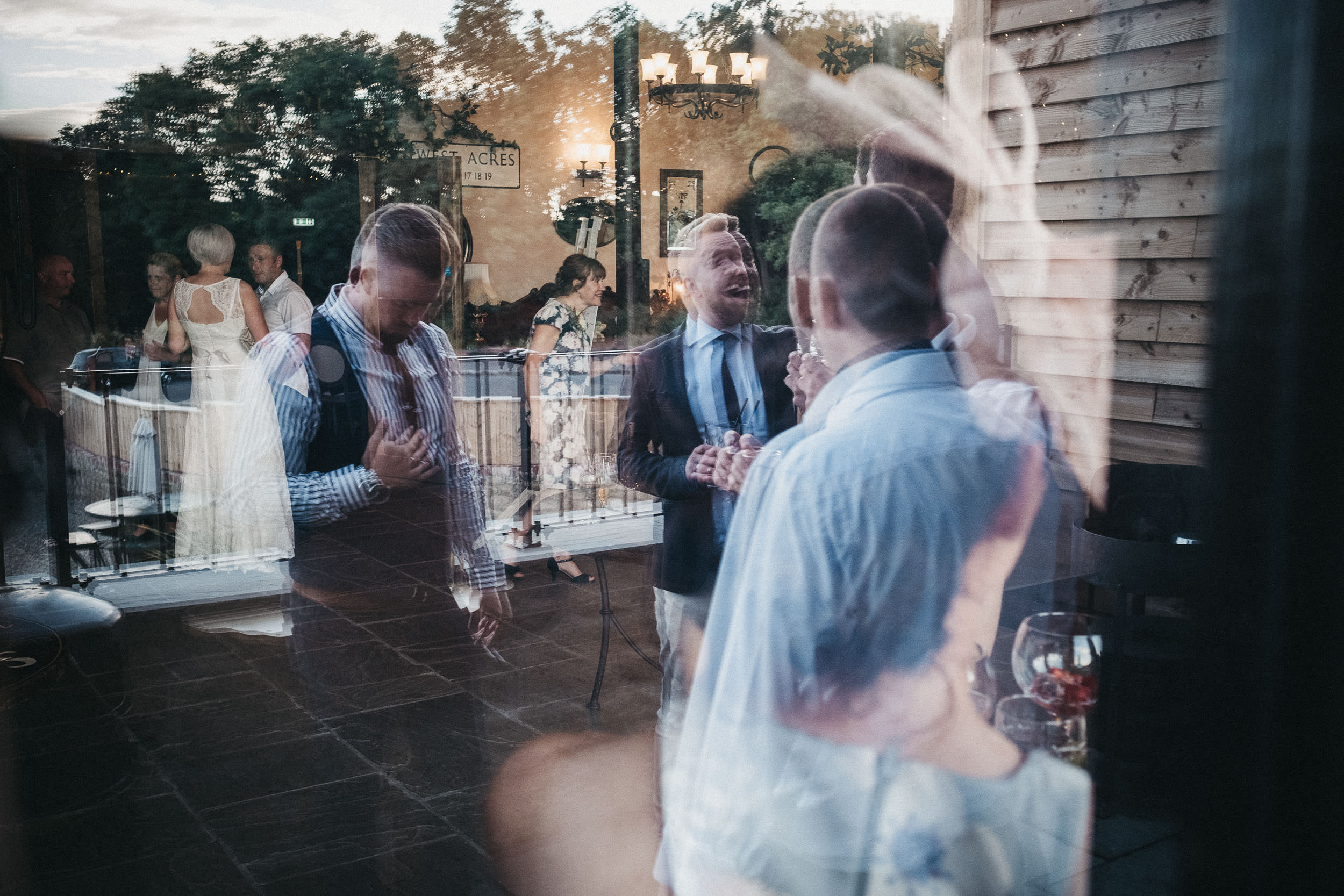 Reflections of bride and guests in window at South Causey Inn