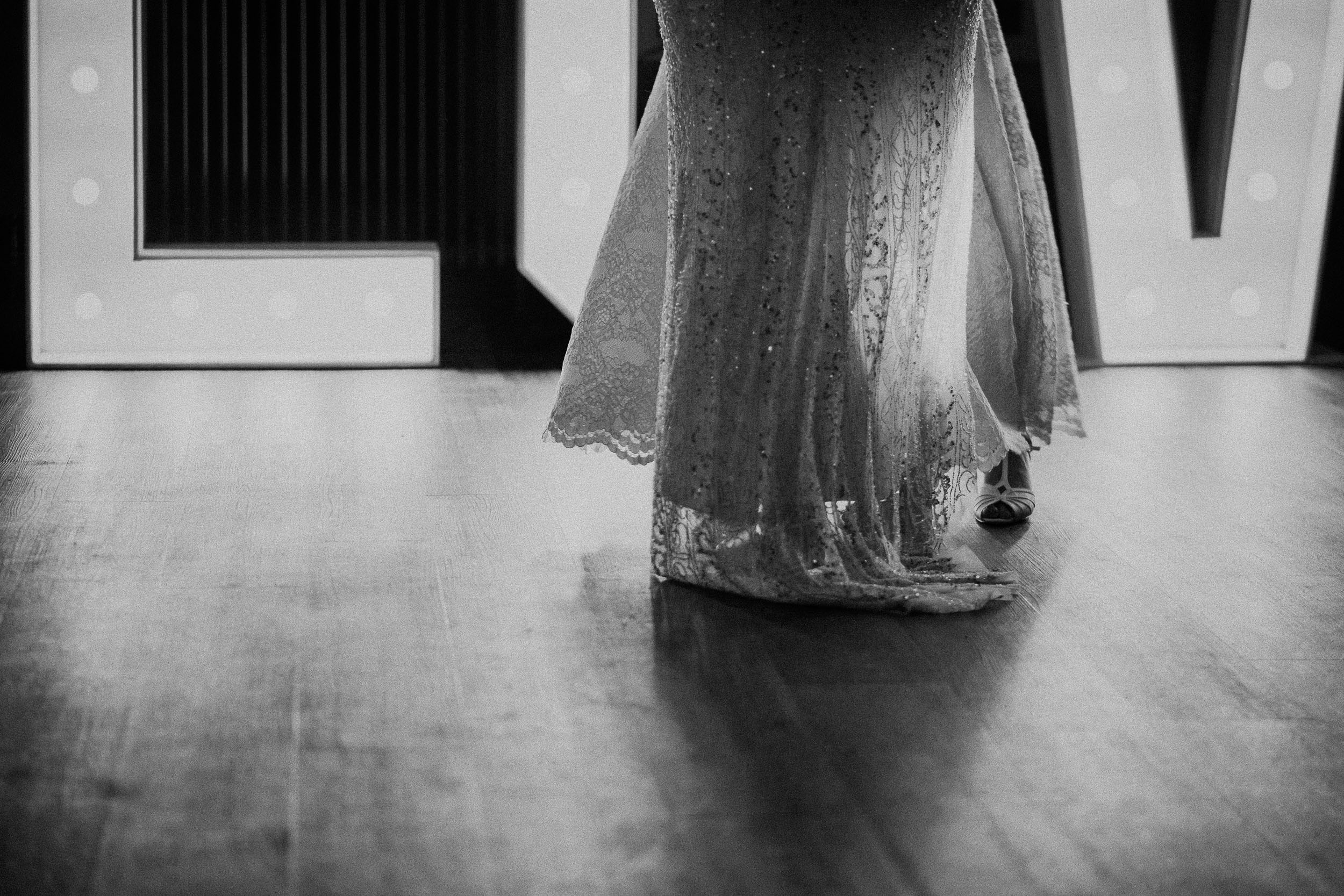 Black and white close up photo of two brides wedding dresses during first dance