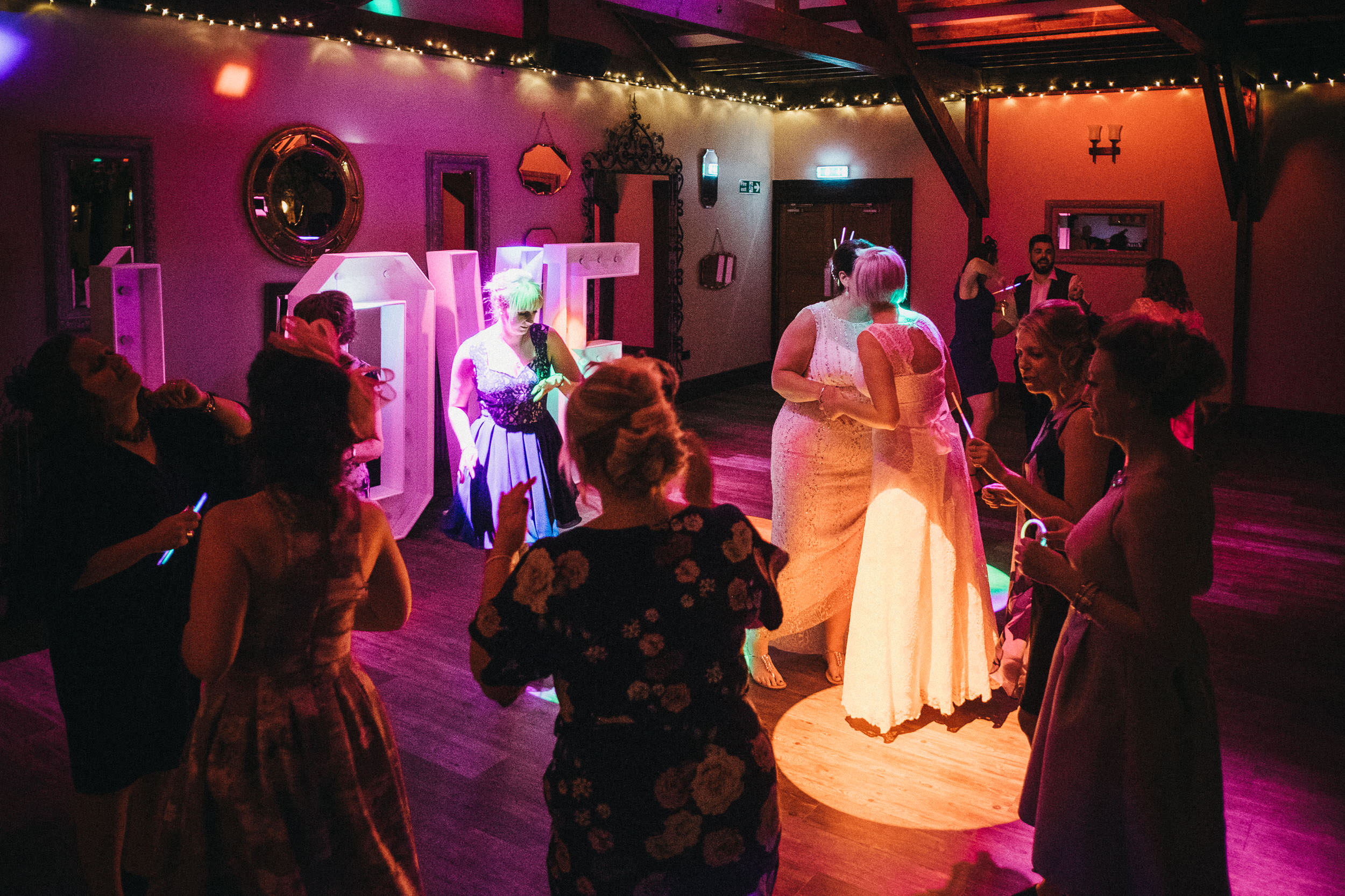 Two brides dance with their wedding guests at South Causey Inn