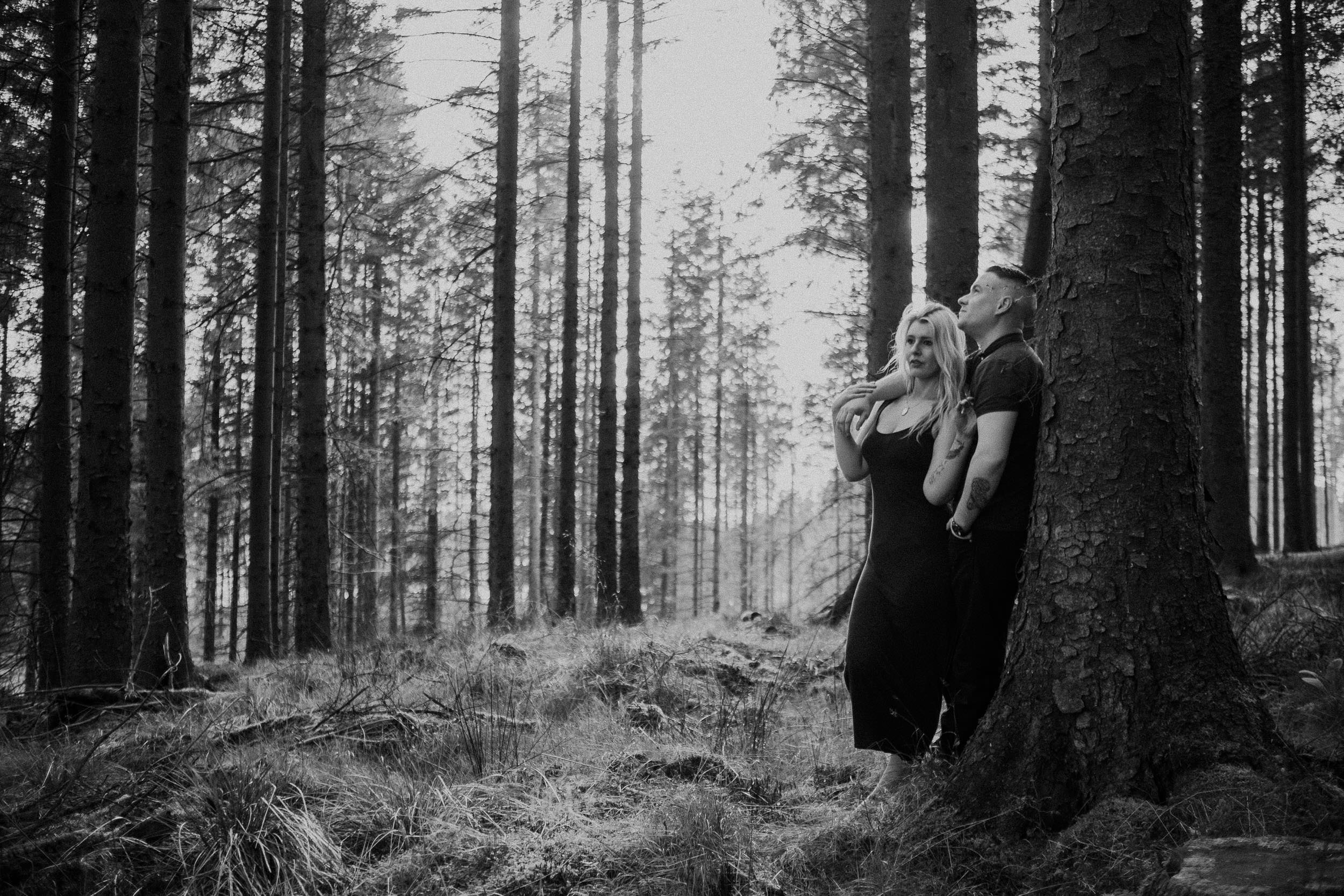 Black and white photo of couple leaning against tree in Kielder Forest