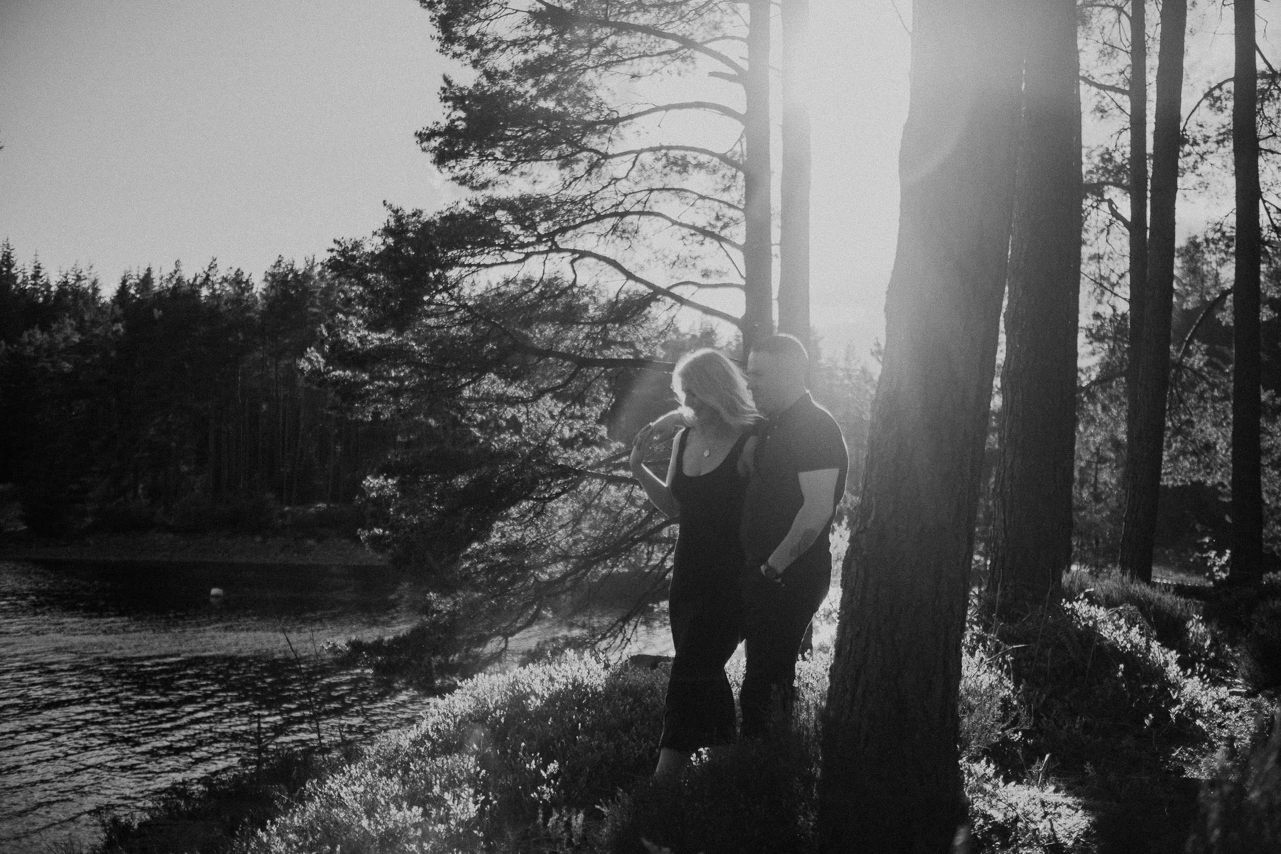 Black and white photo of couple walking through forest with sun shining behind