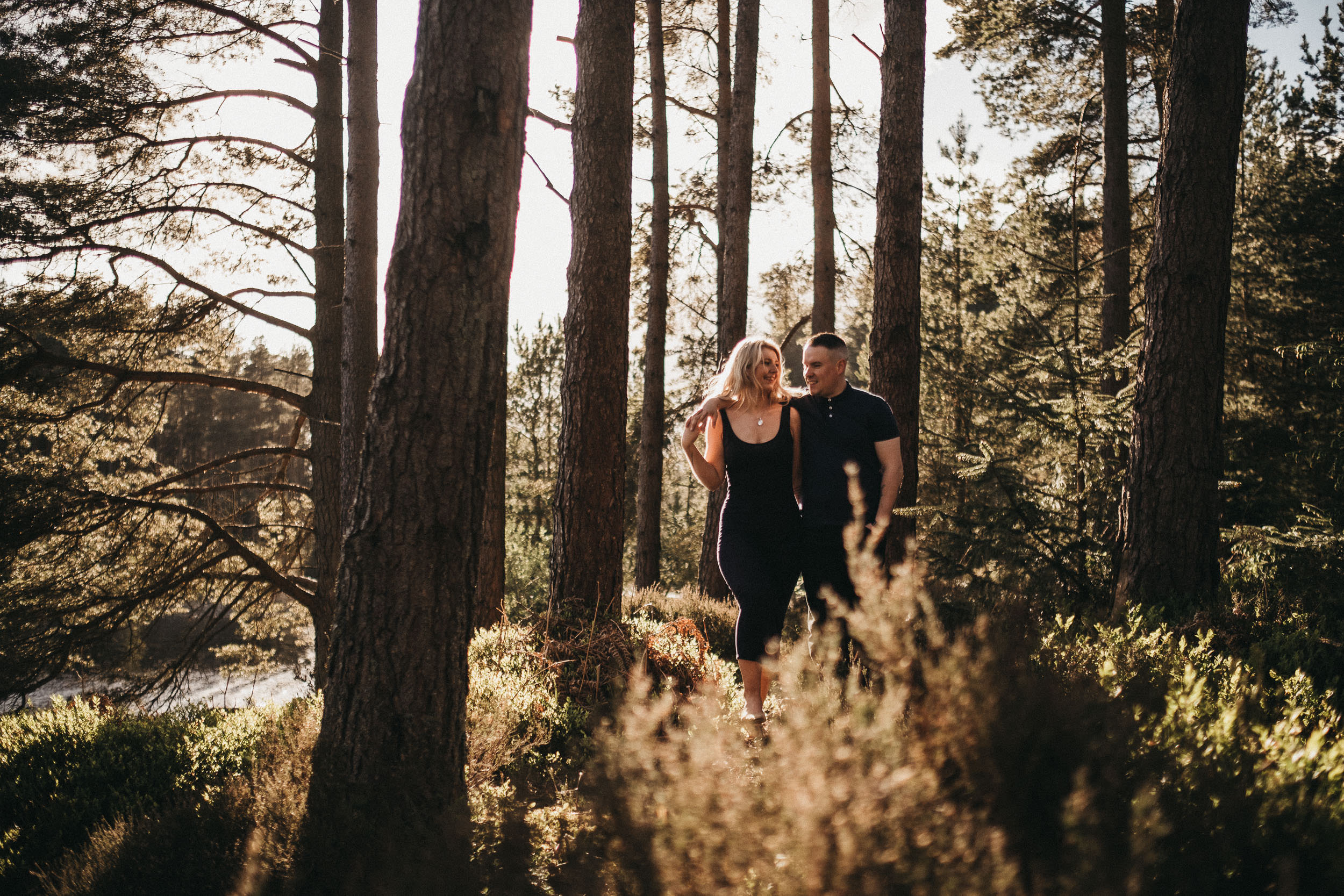 Couple walk through Kielder Forest drenched in sunlight