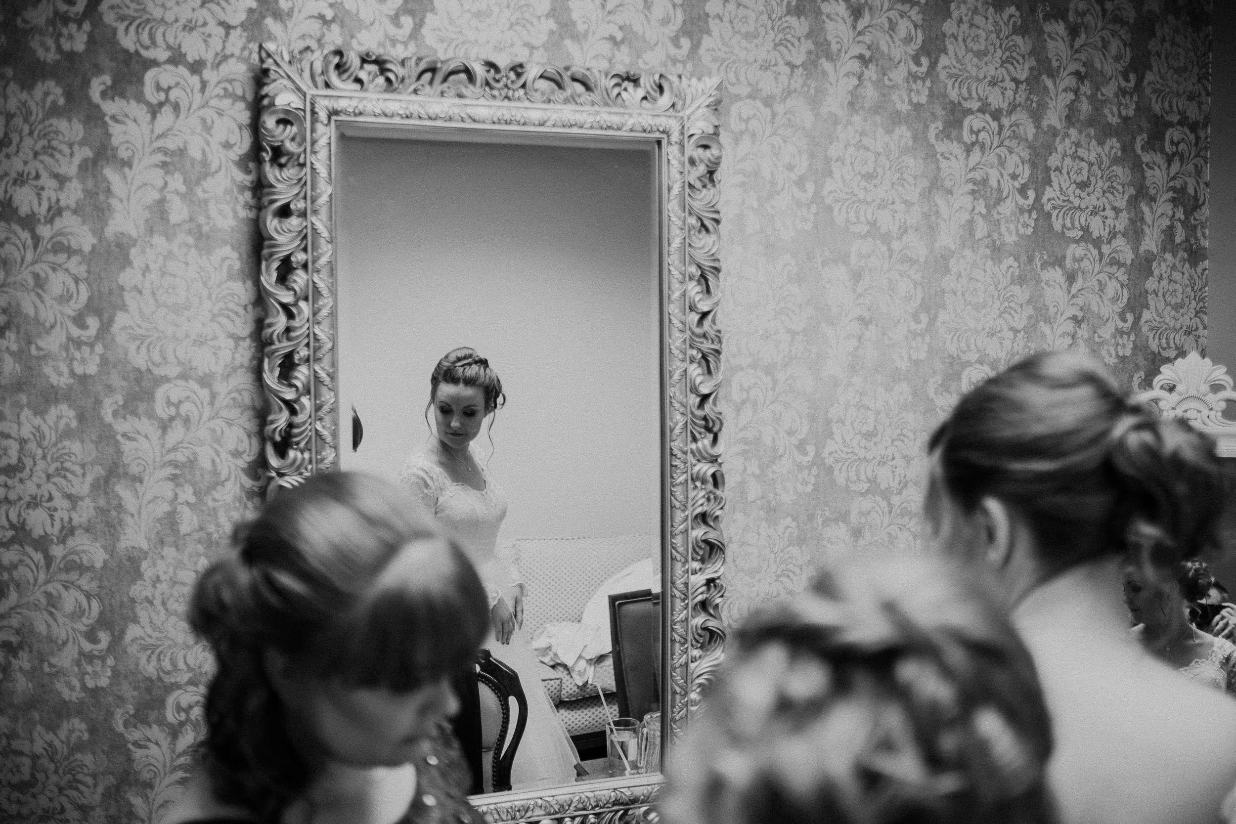 Black and white photo of bride reflected in window while getting ready
