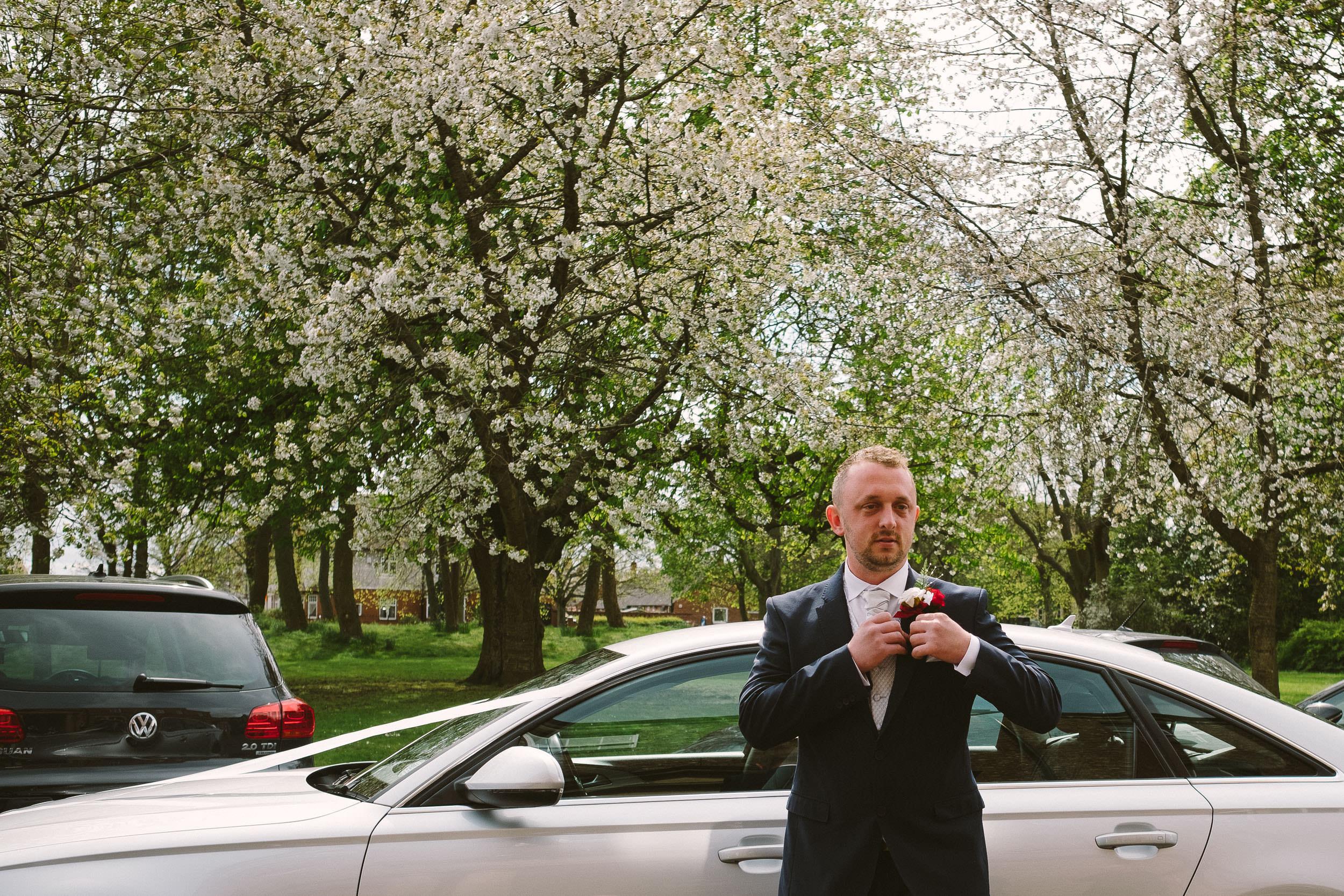 Groom adjusting buttonhole as he arrives at Wallsend Hall