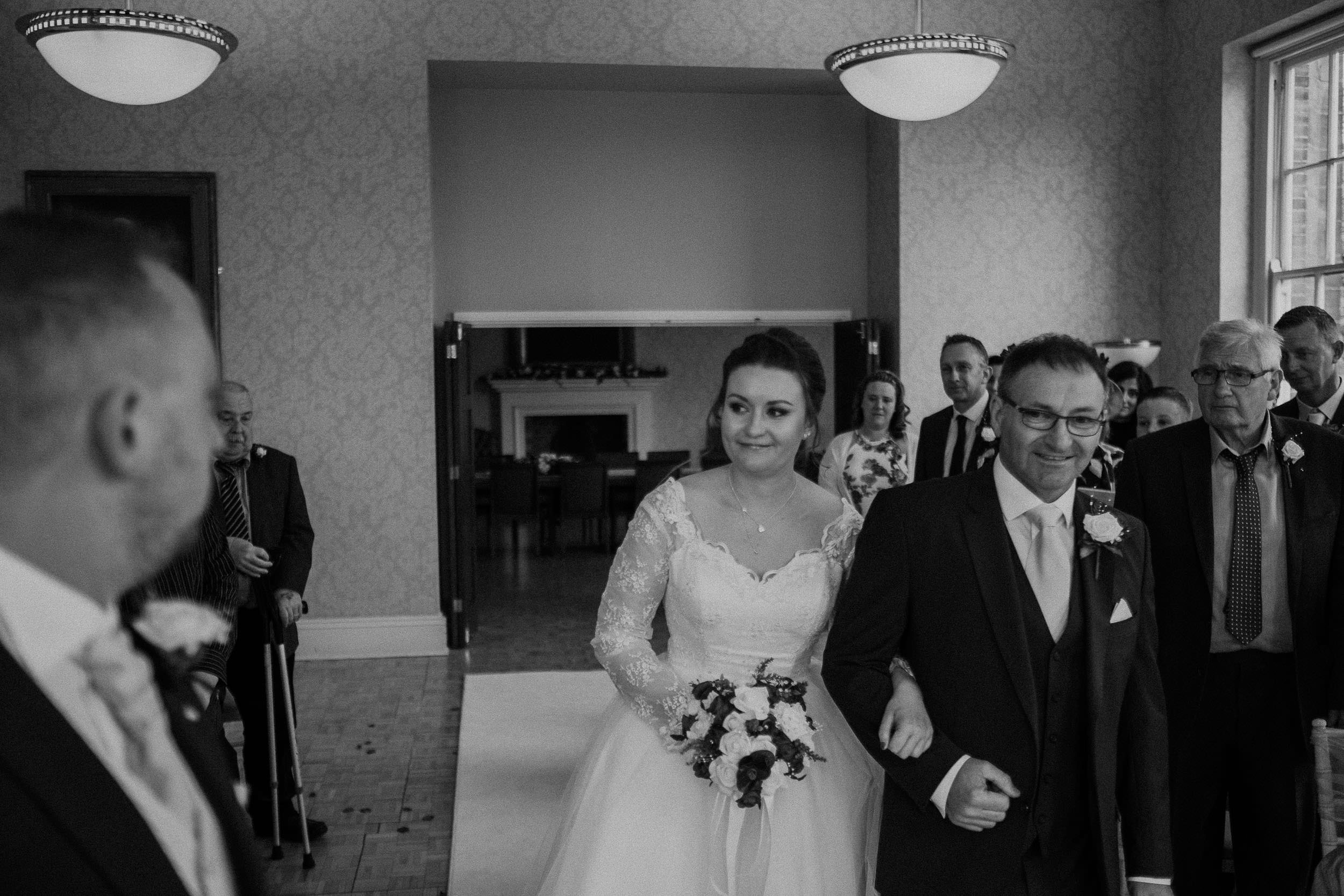 Black and white photo of bride smiling at groom as she arrives for the wedding ceremony