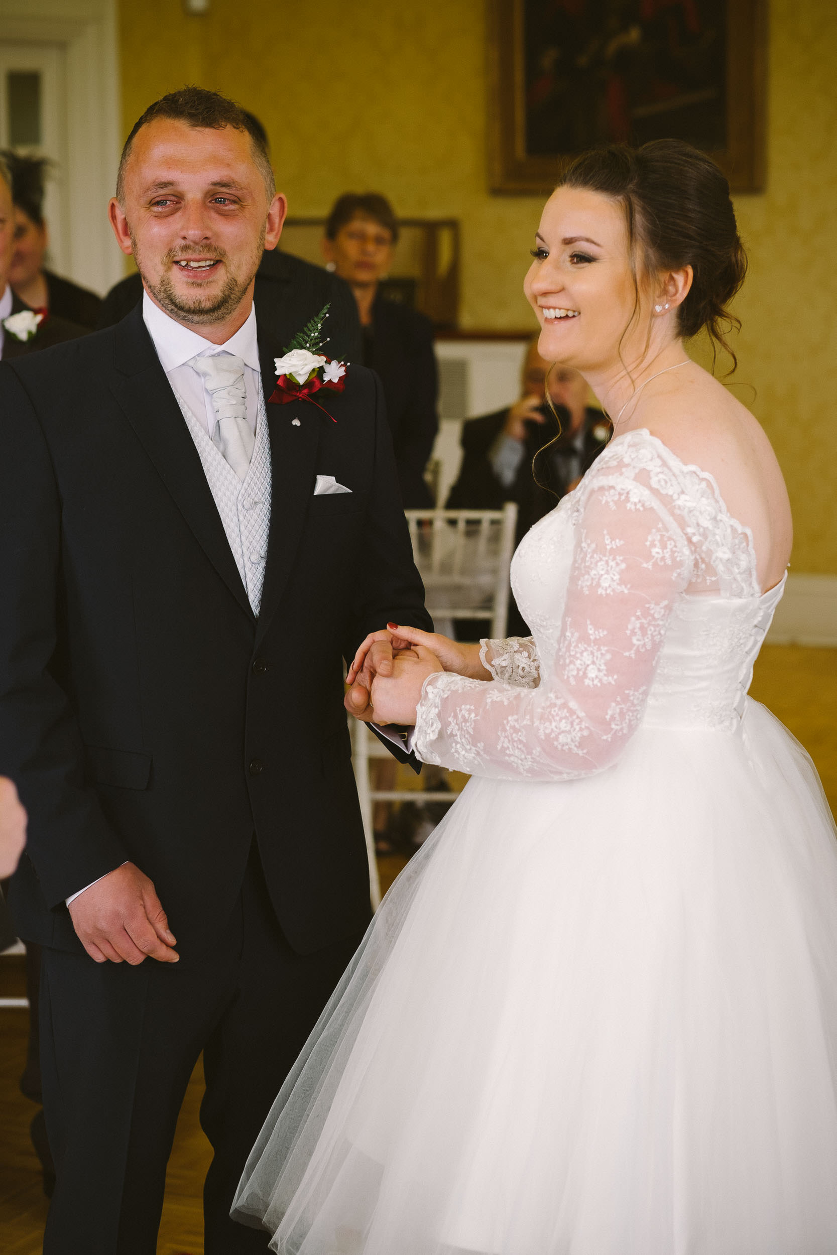 Bride laughing and groom emotional during wedding ceremony