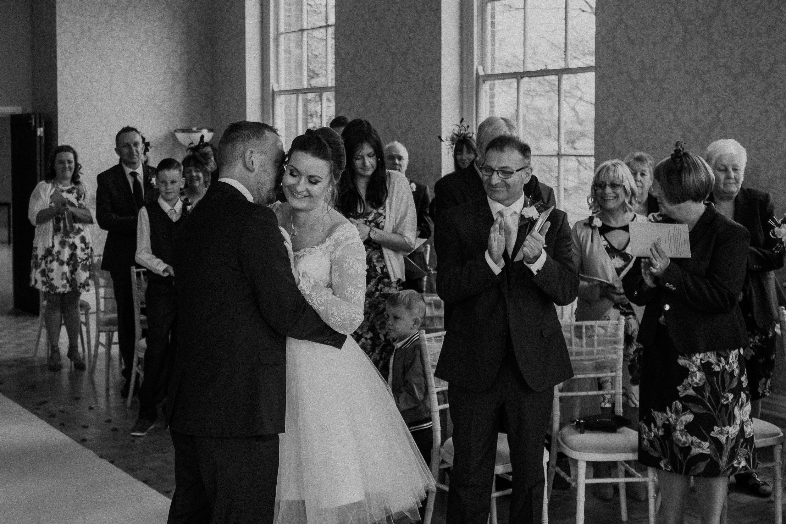 Black and white photo of bride and groom hugging while guests applaude