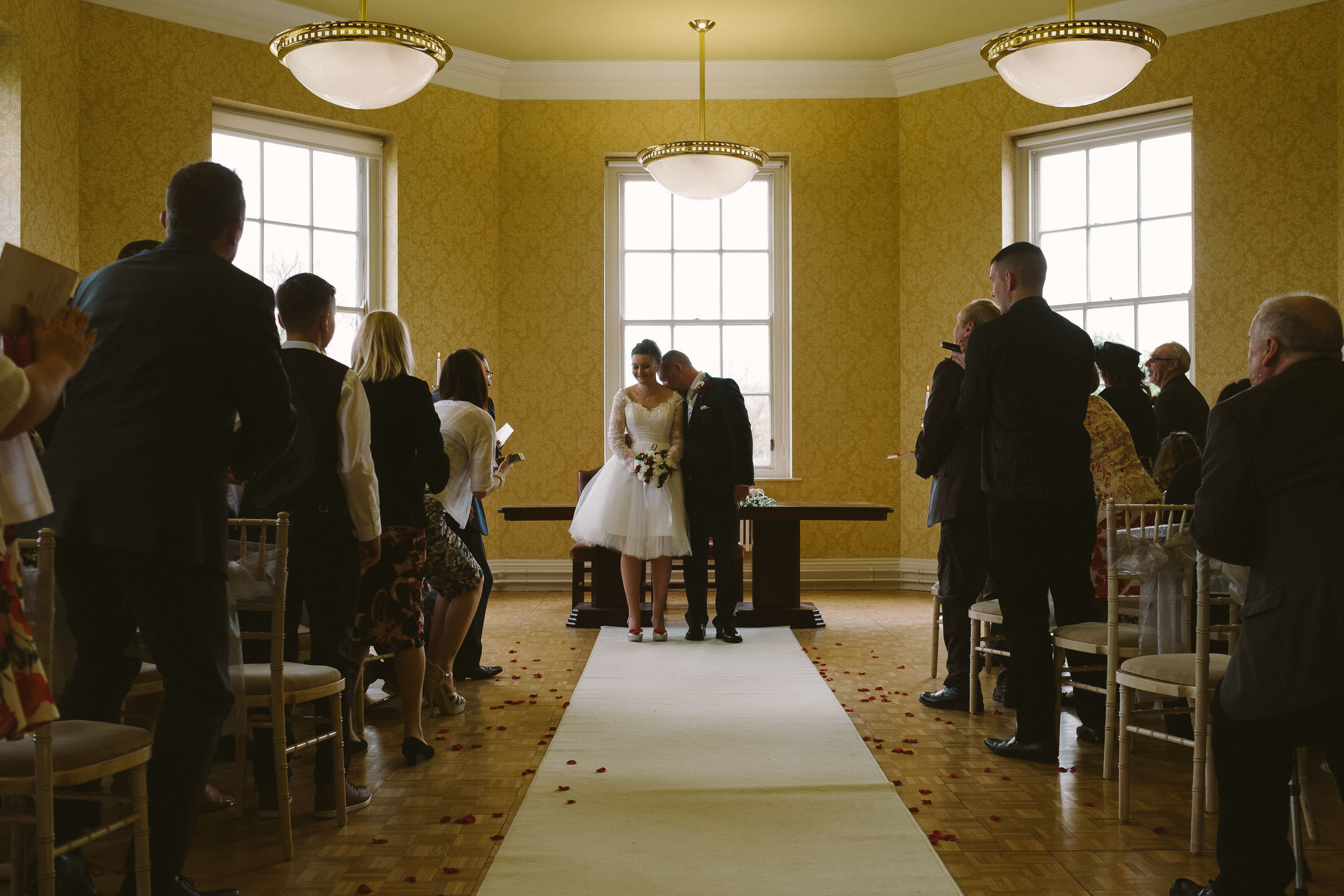 Groom nuzzles brides neck at end of wedding ceremony