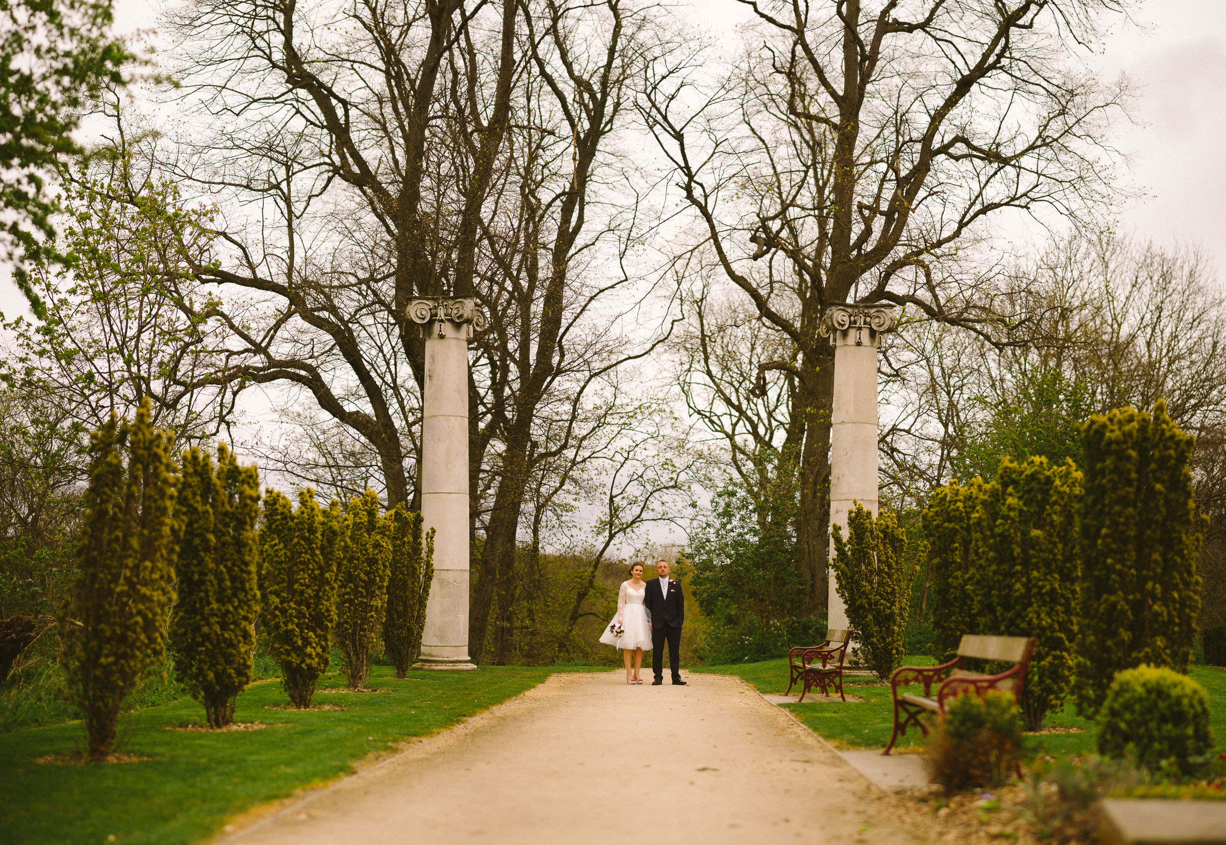 Bride and groom pose with Roman Columns in grounds of Wallsend Hall